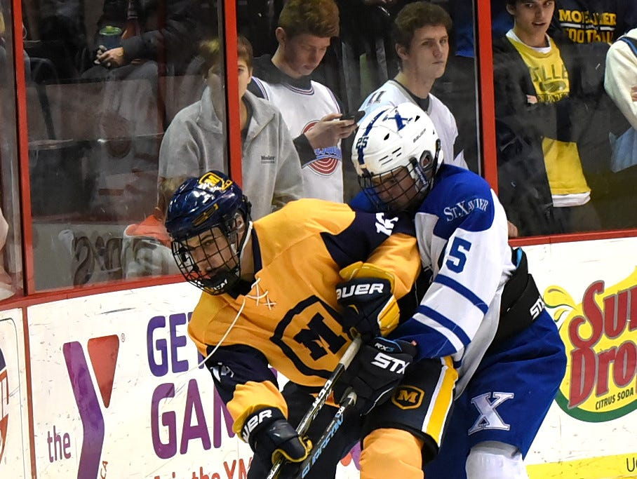 Moeller's Jarrod Gorczynski (17) arrests control of the puck from St. Xavier's Nick DeCarlo at US Bank Arena, December 7, 2018.