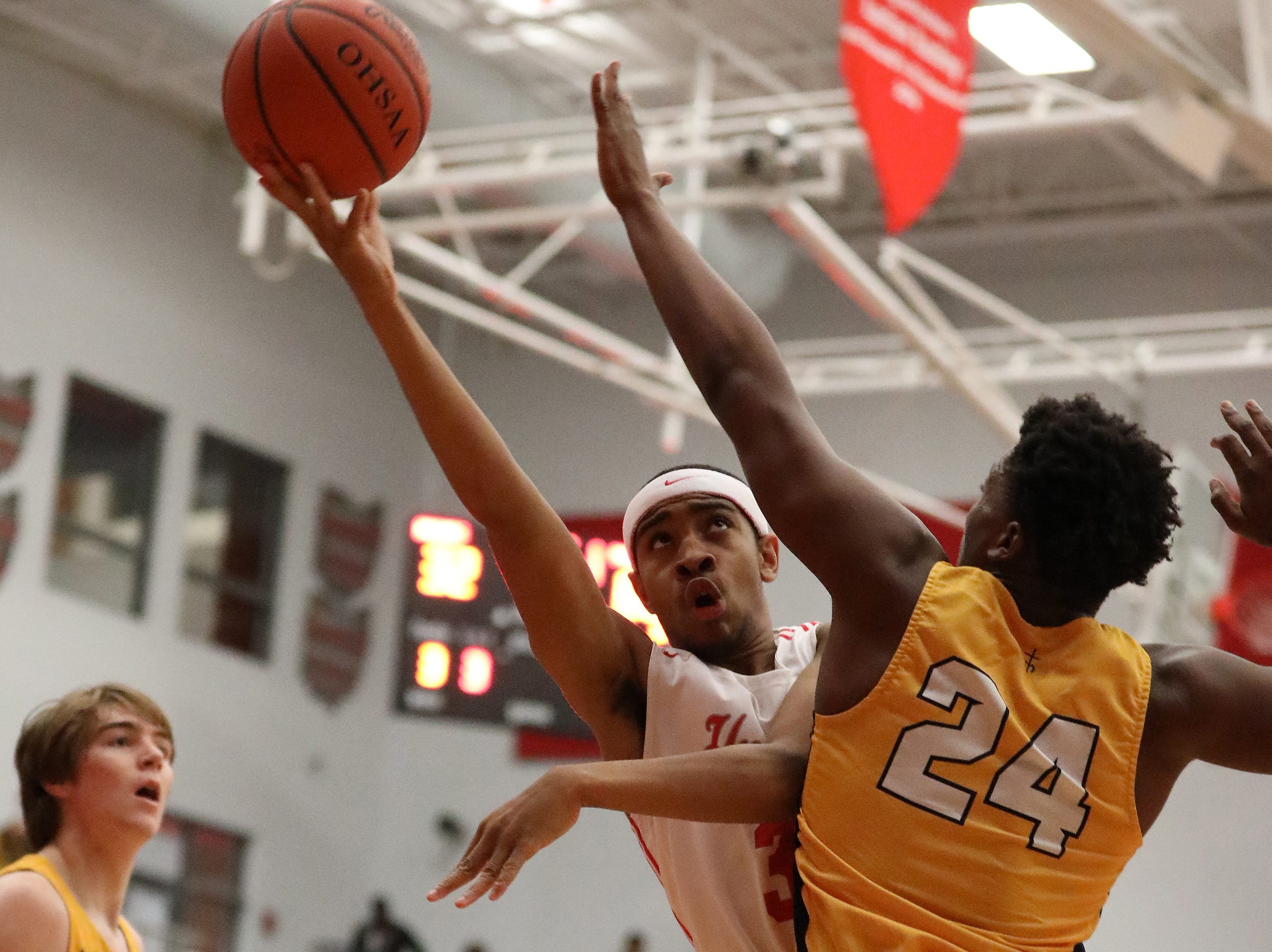 Hughes' Tyon Thompson drives to the basket during their basketball game against Moeller, Friday, Dec. 7, 2018.
