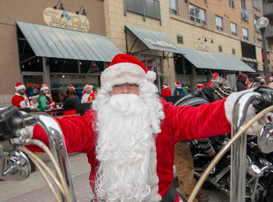 Cincinnati SantaCon 2018 brought hundreds of people dressed as Santa Claus and other Christmas characters to The Banks to spread good cheer and charity. Jerry Frazier enjoys a ride on his Harley dressed as Santa Claus.