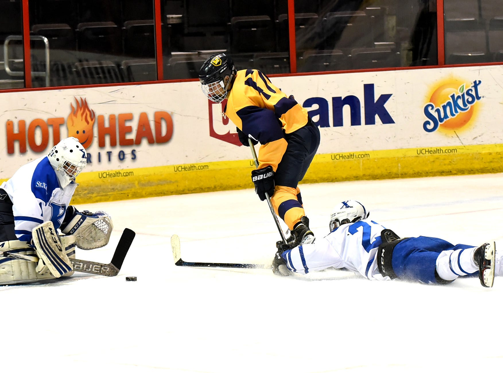 Jordy Walter (center) of Moeller tries to work in a shot on goal between St. Xavier Goalie Bailey Hammons and Tanner Morreale at US Bank Arena, December 7, 2018.