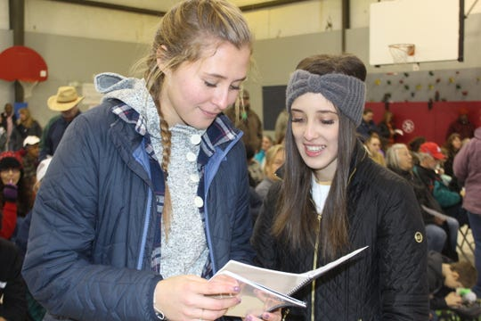 Lead United Student Service Ambassadors Morgan Crowley and Ahna Herrera examine the cookbook they helped develop and distribute to people in need.