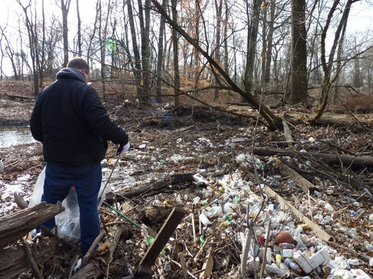 A volunteer sifting through pollution in the Green Brook on Dec. 8, 2018.