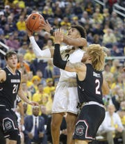 Michigan Wolverines guard Jordan Poole scores against South Carolina Gamecocks guard Hassani Gravett during the second half Saturday, Dec. 8, 2018 at the Crisler Center in Ann Arbor.
