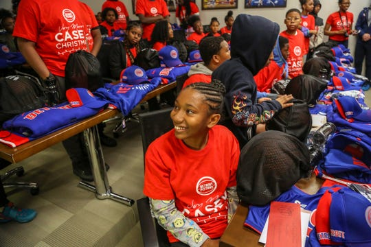 """Alexie Davis, 13, of Detroit, smiles after saying, """"This is going to be the best day ever,"""" after receiving personalized Detroit Pistons jerseys, hats, a basketball, and gifts from players like headphones from Andre Drummond and basketball shoes from Langston Galloway, during the event """"Very Merry Casey Christmas"""" on Saturday, Dec. 8, 2018. Children with incarcerated parents from the Pure Heart Foundation spent the morning at the Pistons practice facility in Auburn Hills."""
