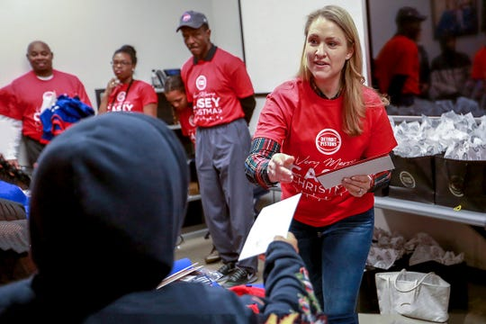 "Brenda Casey, wife of Detroit Pistons coach Dwane Casey, hands out envelopes with $100 cash to children with incarcerated parents from the Pure Heart Foundation at the Pistons practice facility in Auburn Hills, during the event ""Very Merry Casey Christmas"" on Saturday, Dec. 8, 2018."