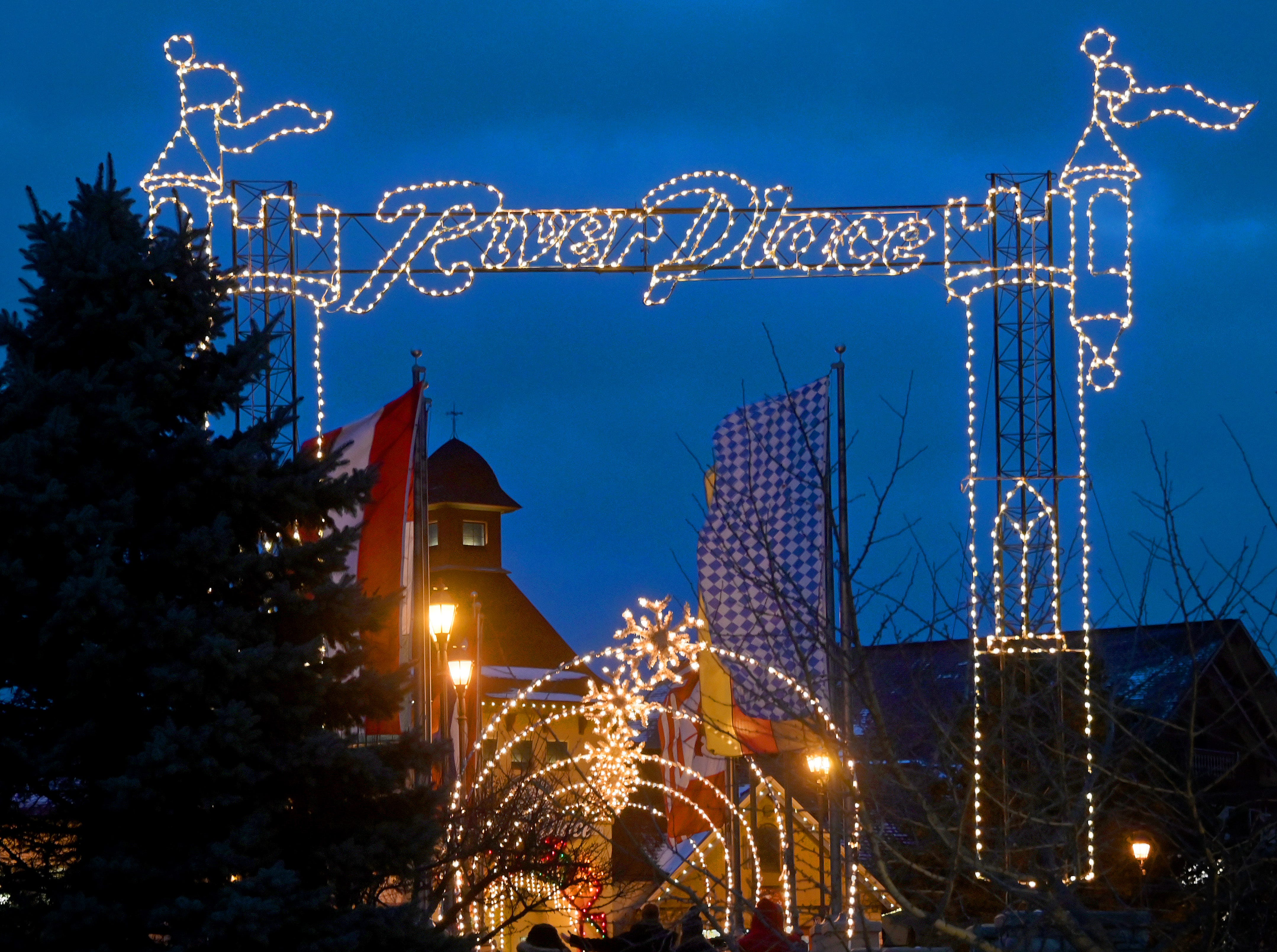 Holiday visitors cross a whimsically lighted pedestrian bridge over the Cass River in Frankenmuth.