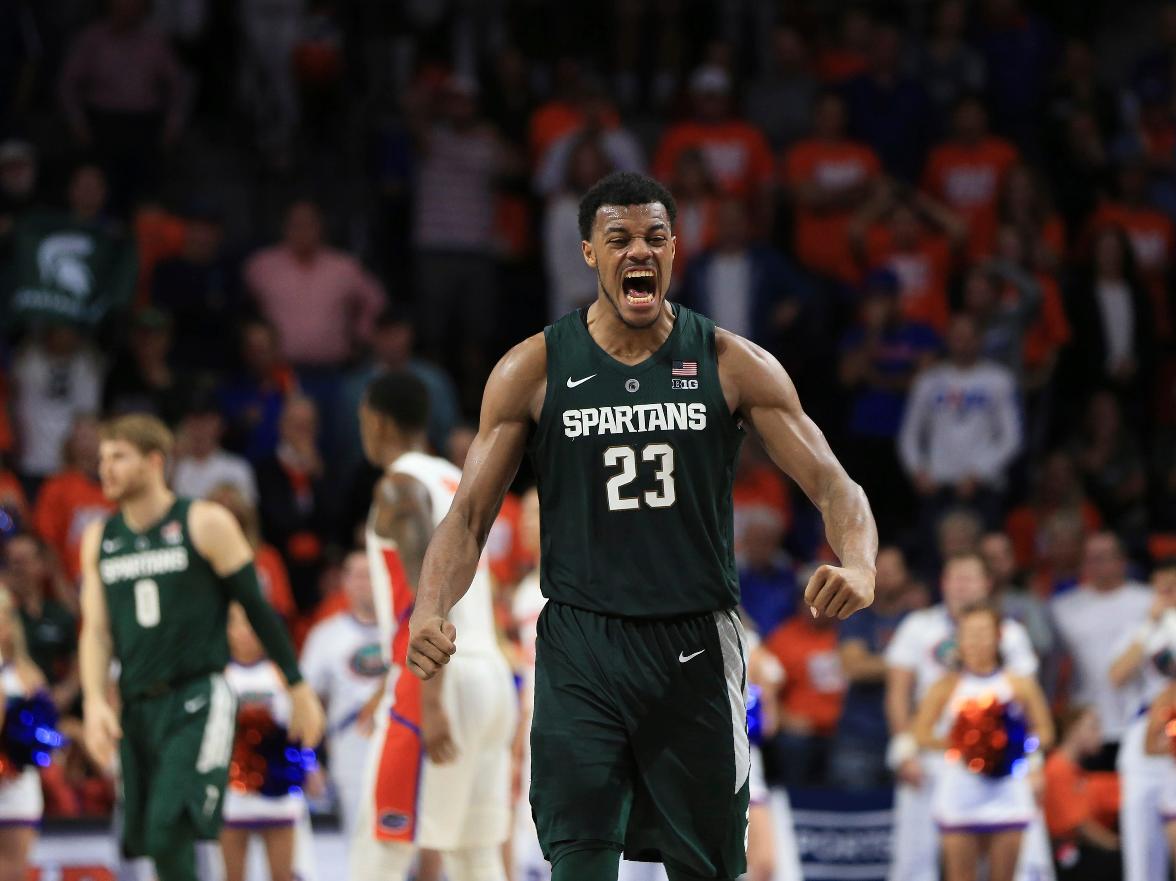 Michigan State forward Xavier Tillman (23) celebrates after a dunk by forward Kyle Ahrens  late in the second half of  a 63-59 Spartans victory over the Florida Gators Saturday, Dec. 8, 2018, in Gainesville, Fla.
