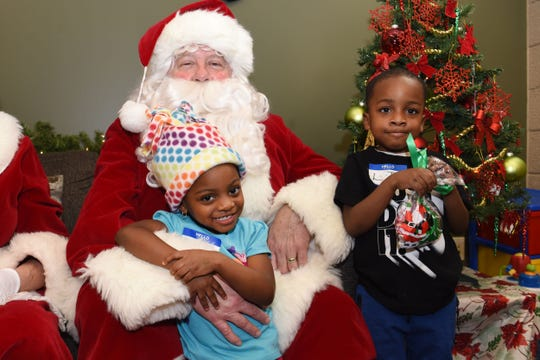 Lyric Lyght, 3, of Detroit, and her brother L.J. Lyght receive gifts from Santa Claus and Mrs. Claus during The Logan Foundation's holiday party at the Samaritas Center in Detroit.