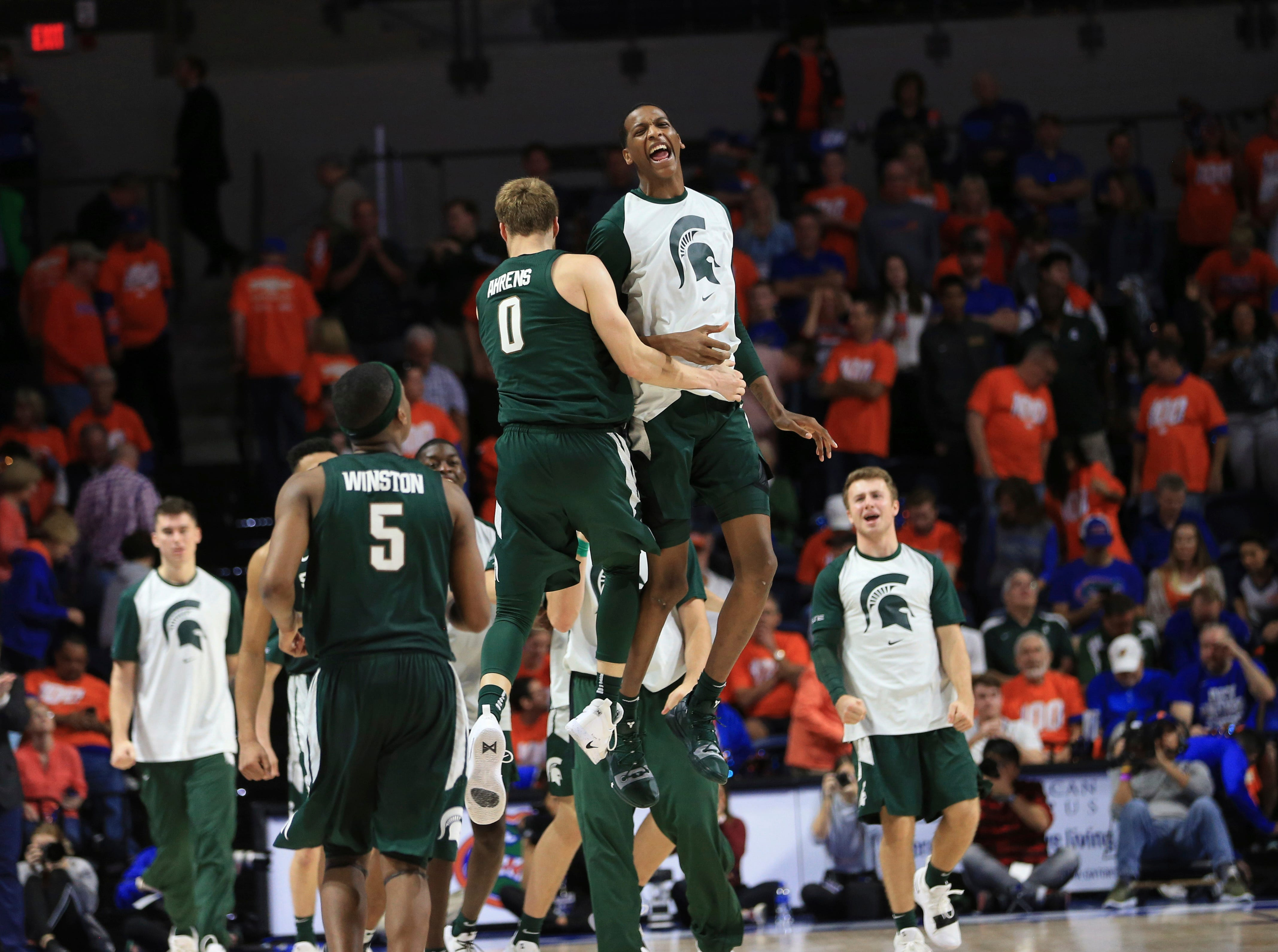 Michigan State forwards Kyle Ahrens (0) and Marcus Bingham Jr. (top) celebrate after Michigan State defeated Florida 63-59.
