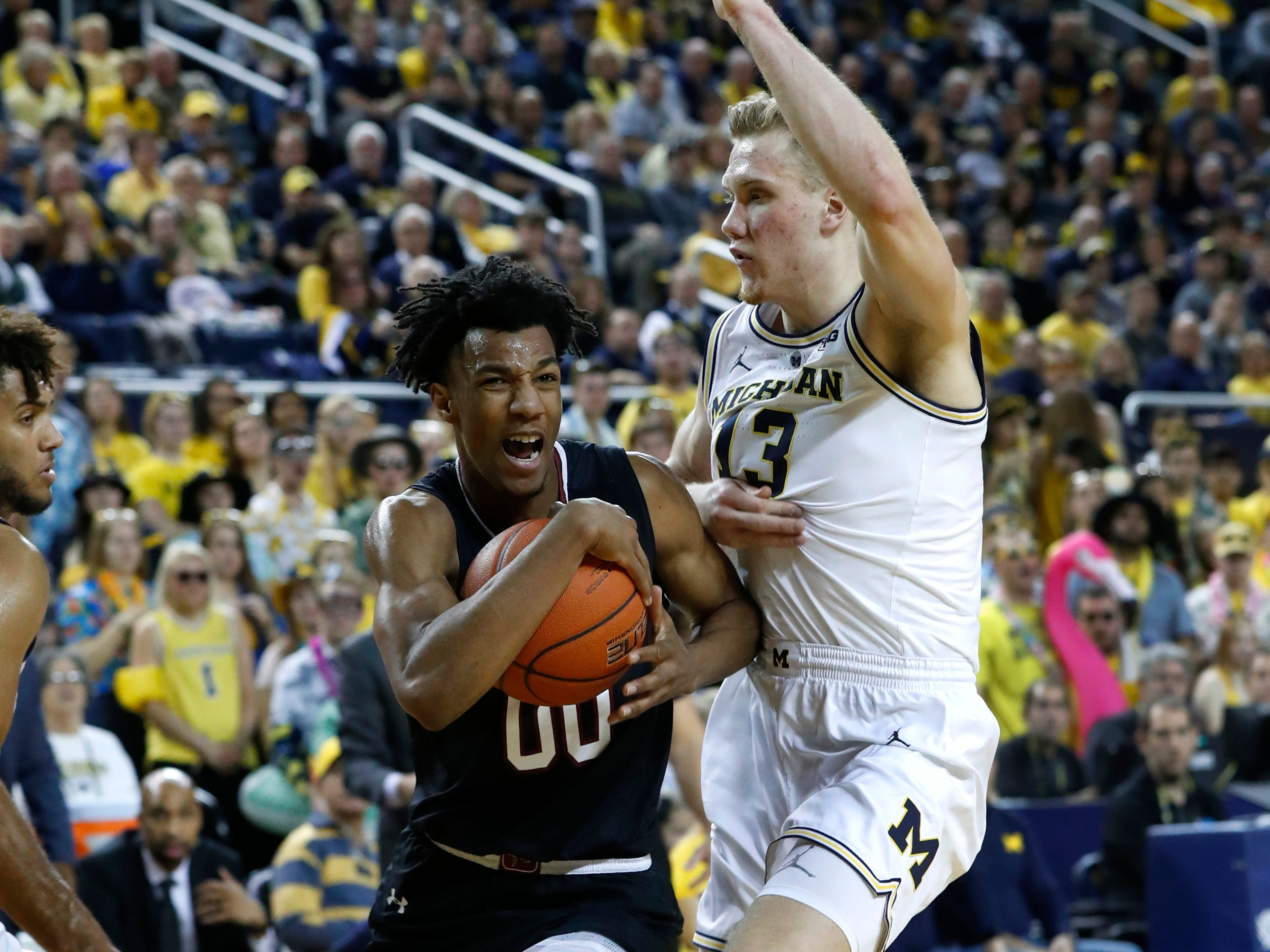South Carolina guard A.J. Lawson (00) drives against Michigan forward Ignas Brazdeikis (13) in the first half.