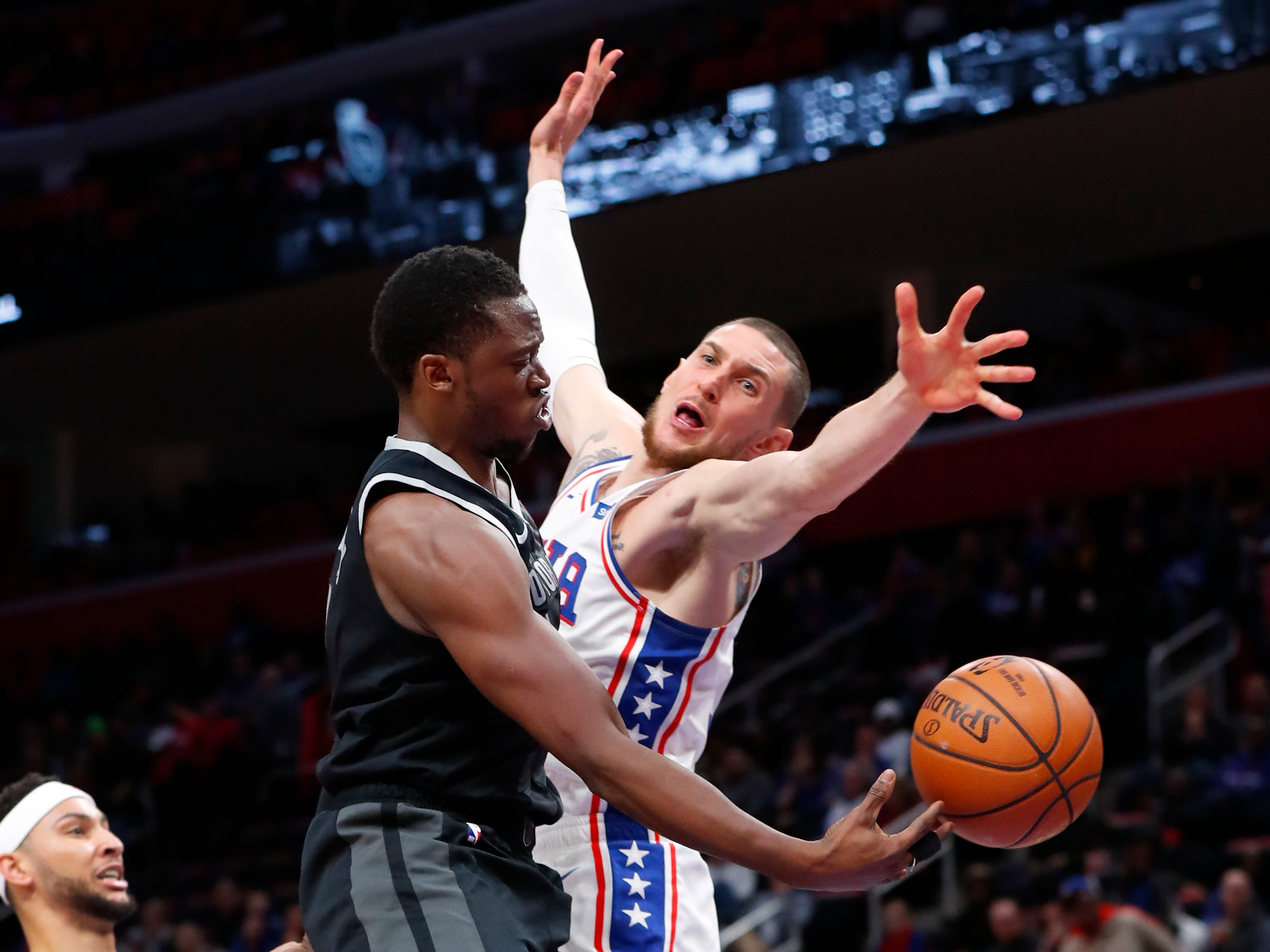 Detroit Pistons guard Reggie Jackson (1) passes around Philadelphia 76ers forward Mike Muscala (31) in the first half of their game in Detroit, Friday, Dec. 7, 2018.