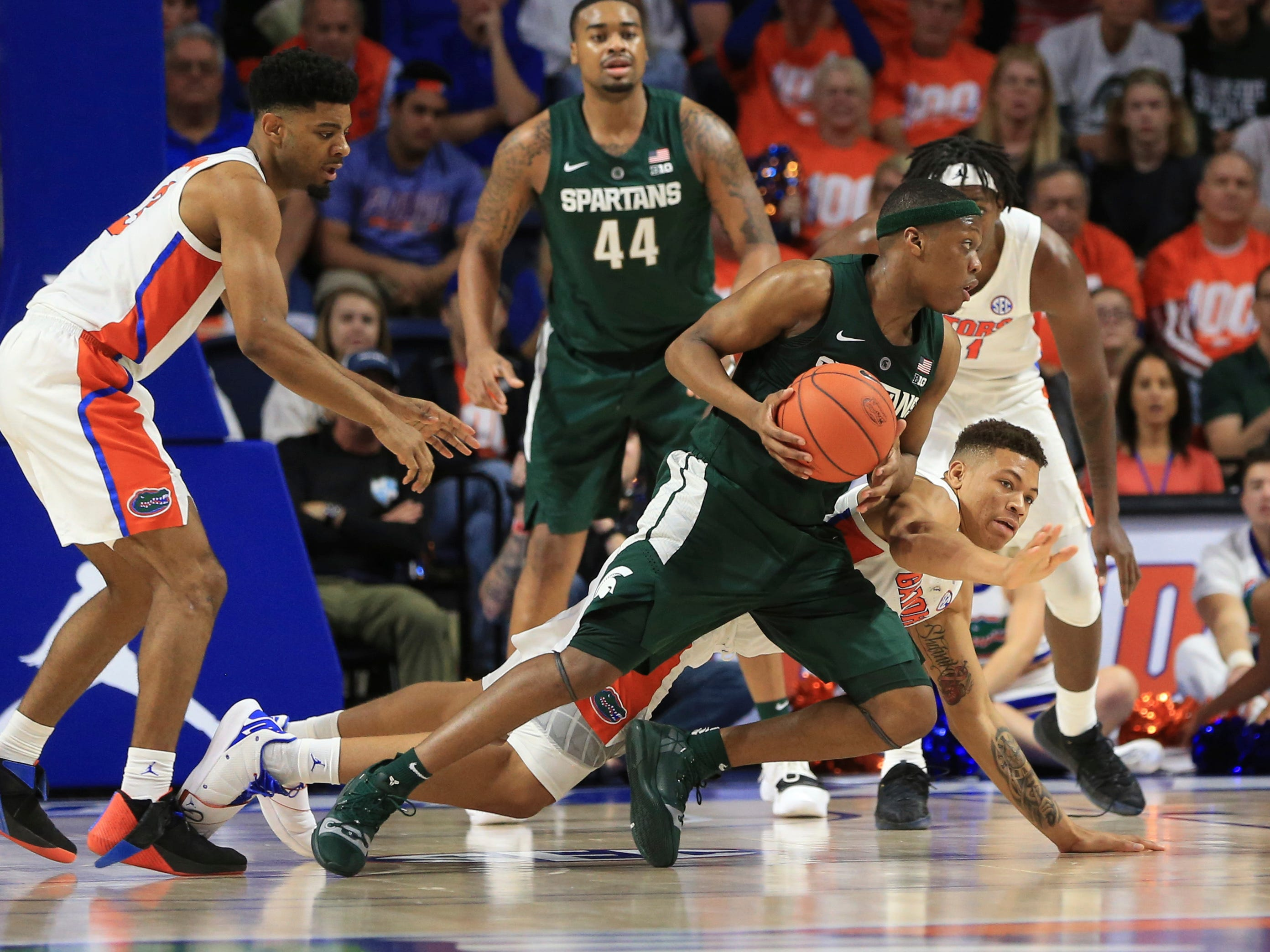 Michigan State guard Cassius Winston (5) comes up with the ball past a diving Florida forward Keyontae Johnson (11) during the second half.