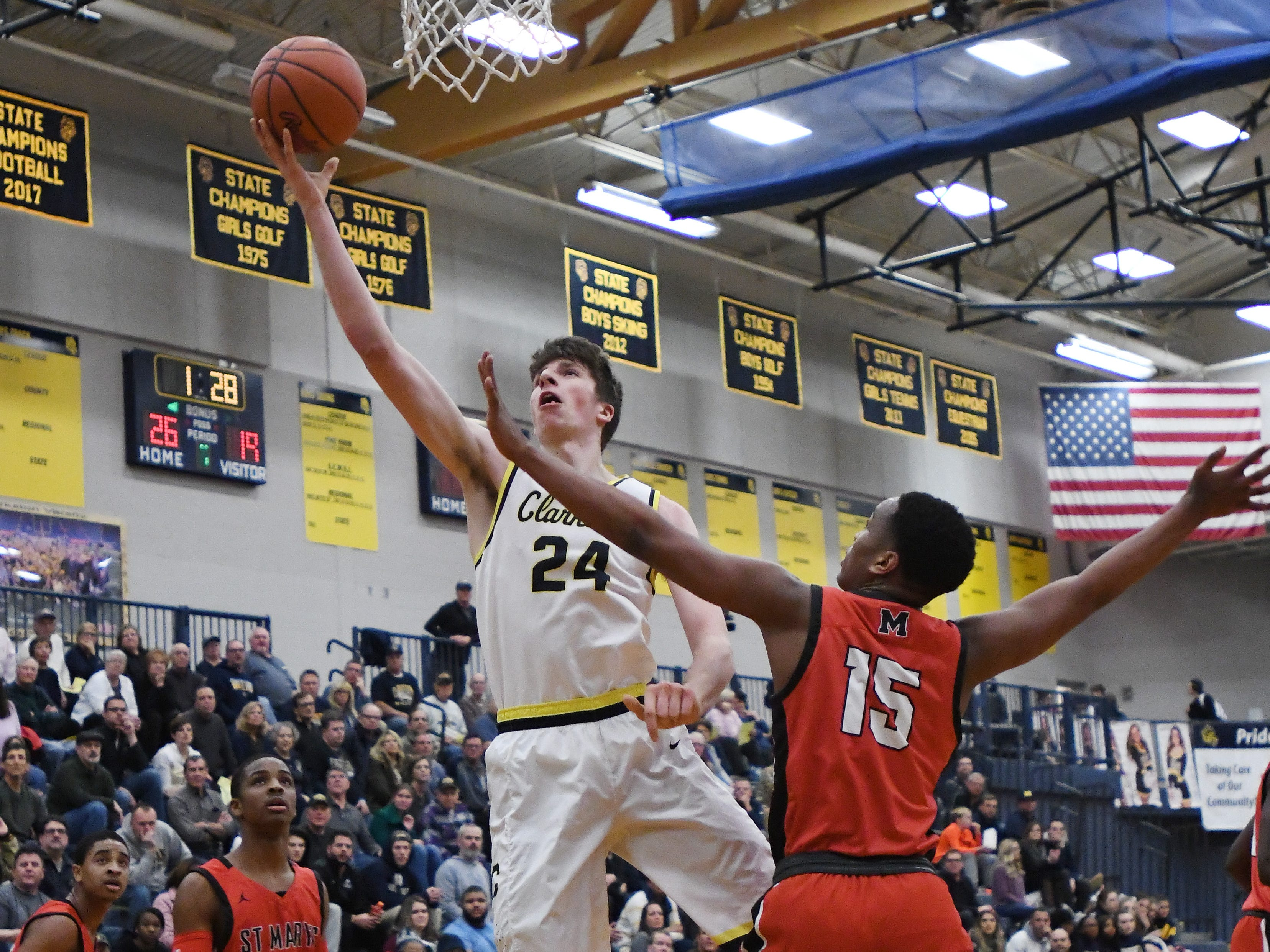 Clarkston's Matt Nicholson lays in two points and draws a foul by St. Mary's DeCorion Temple.