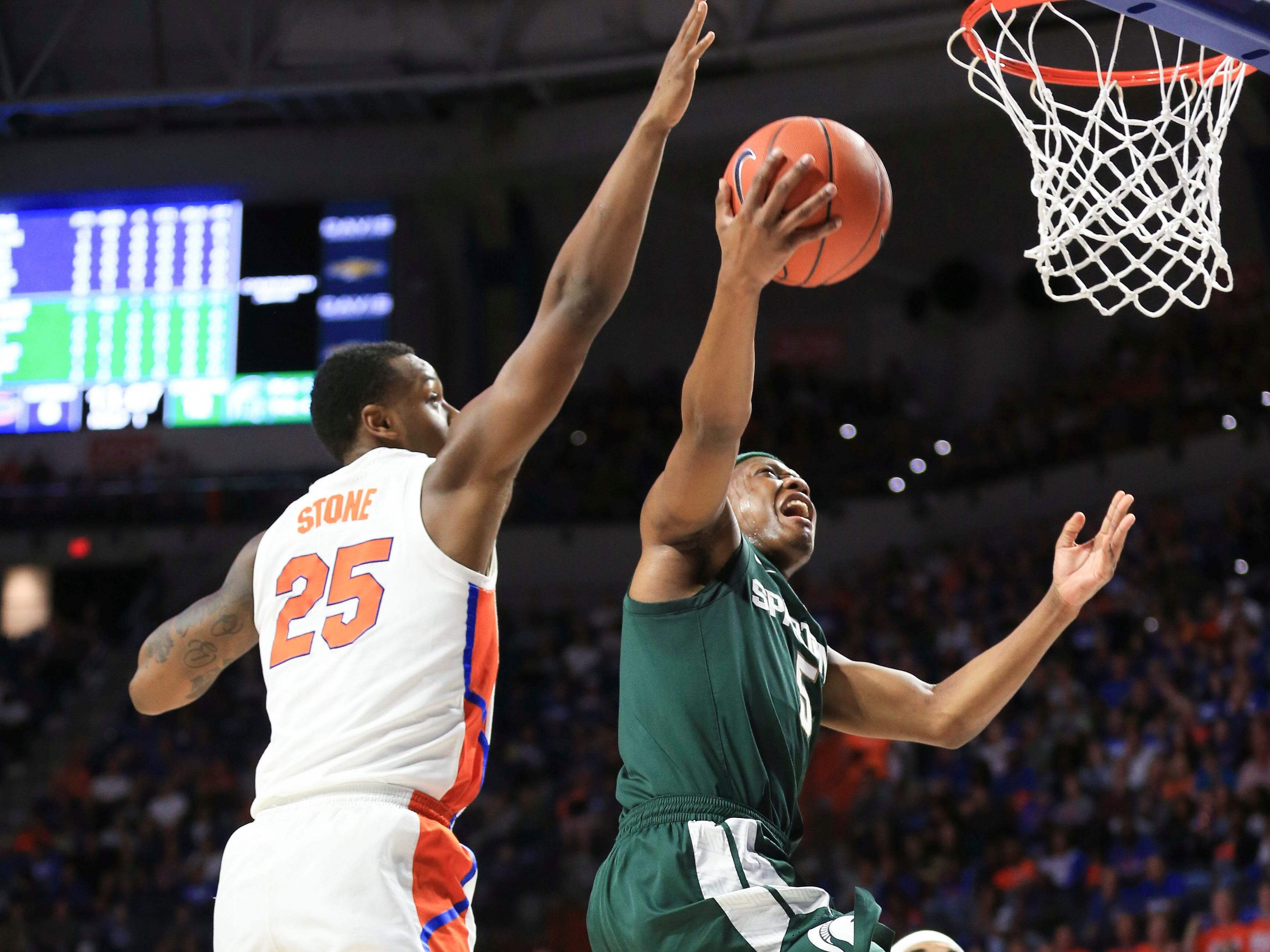 Michigan State guard Cassius Winston (5) makes a layup past Florida forward Keith Stone (25) during the first half.