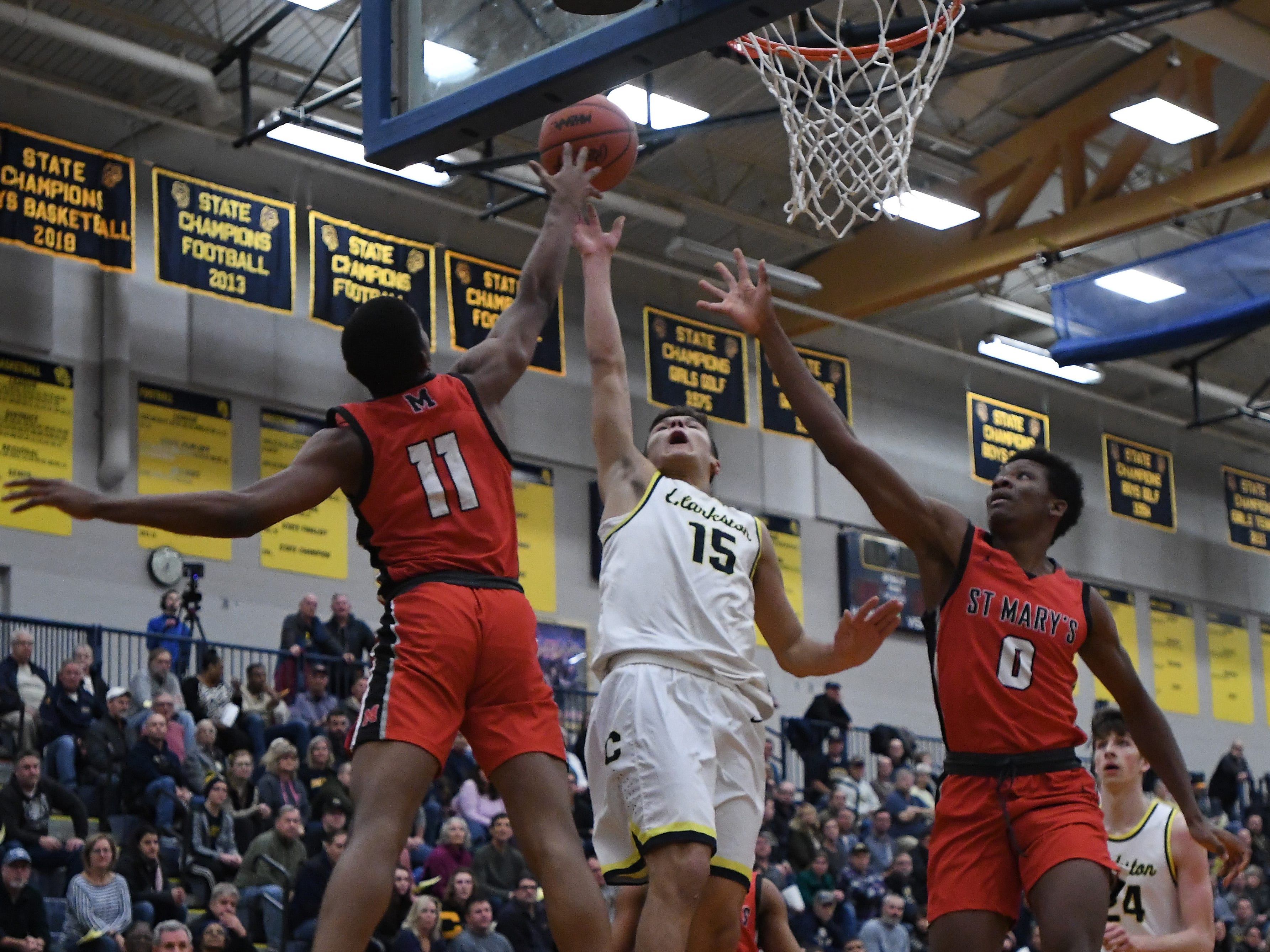 Clarkston's Keegan Wasilk lightly puts up a shot that goes in for two over St. Mary's defense in the first quarter.