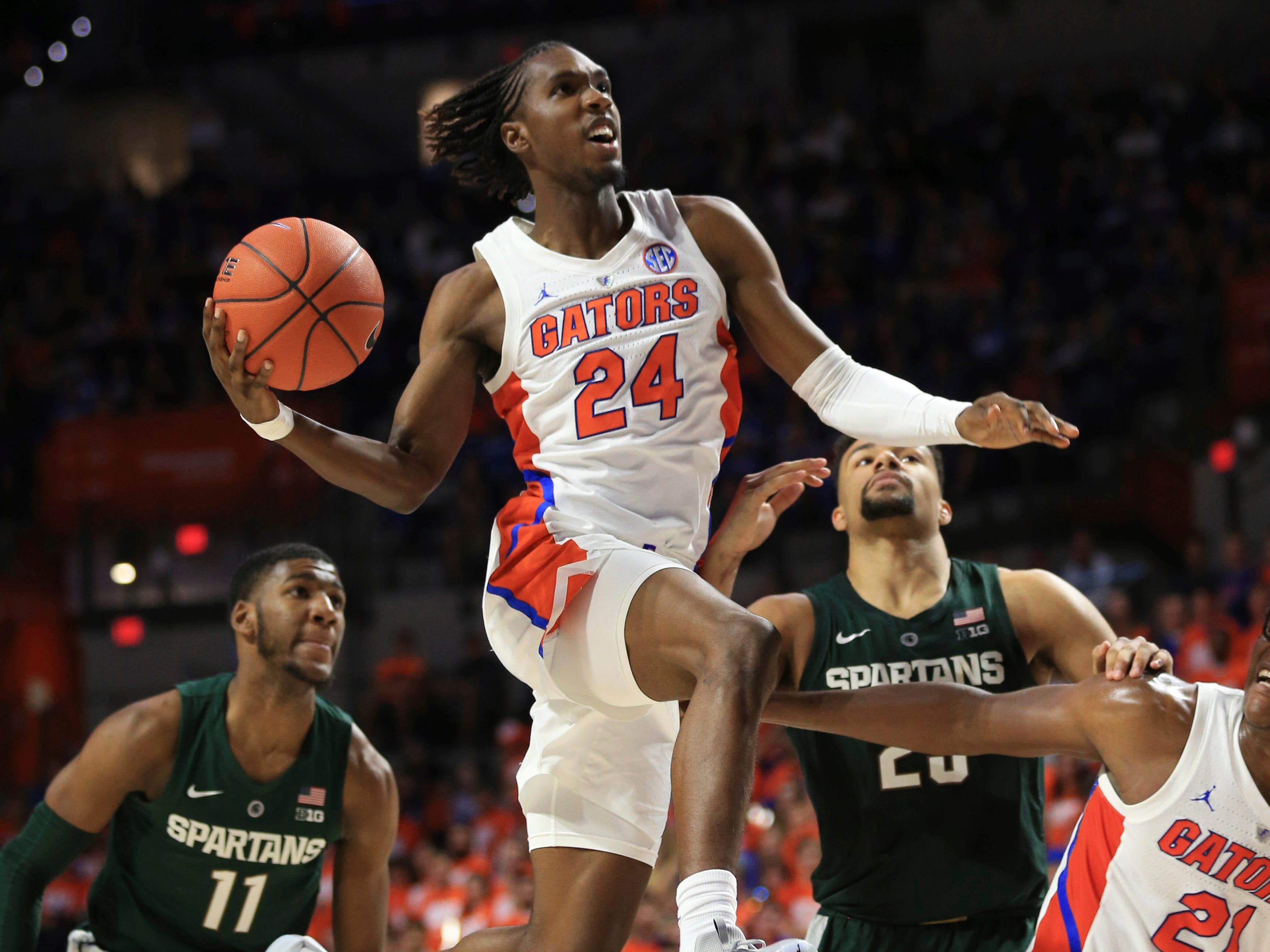 Florida guard Deaundrae Ballard (24) goes up for a shot past Michigan State forward Xavier Tillman (23) and forward Aaron Henry (11) during the second half.
