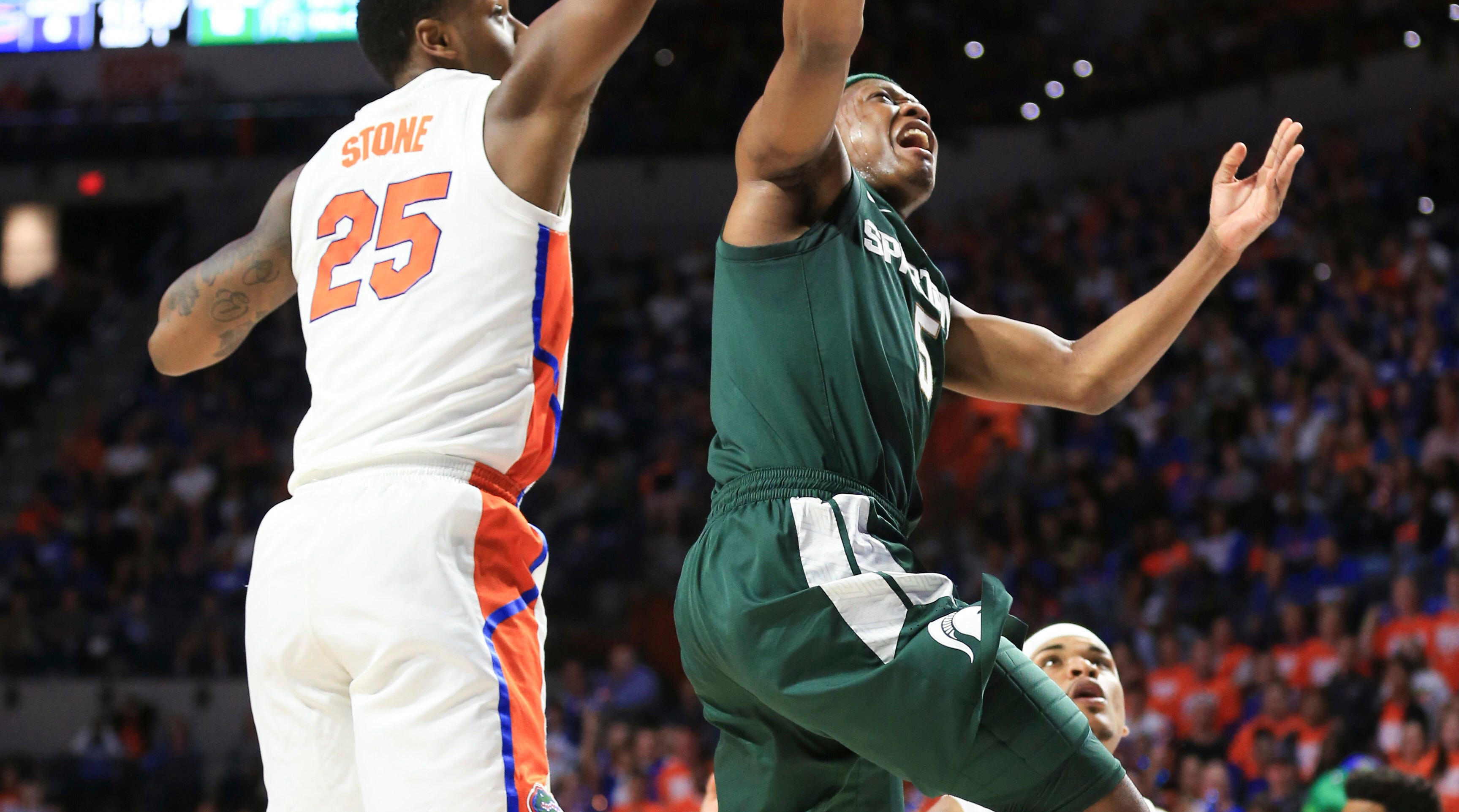 Michigan State guard Cassius Winston  makes a layup past Florida forward Keith Stone during the first half.