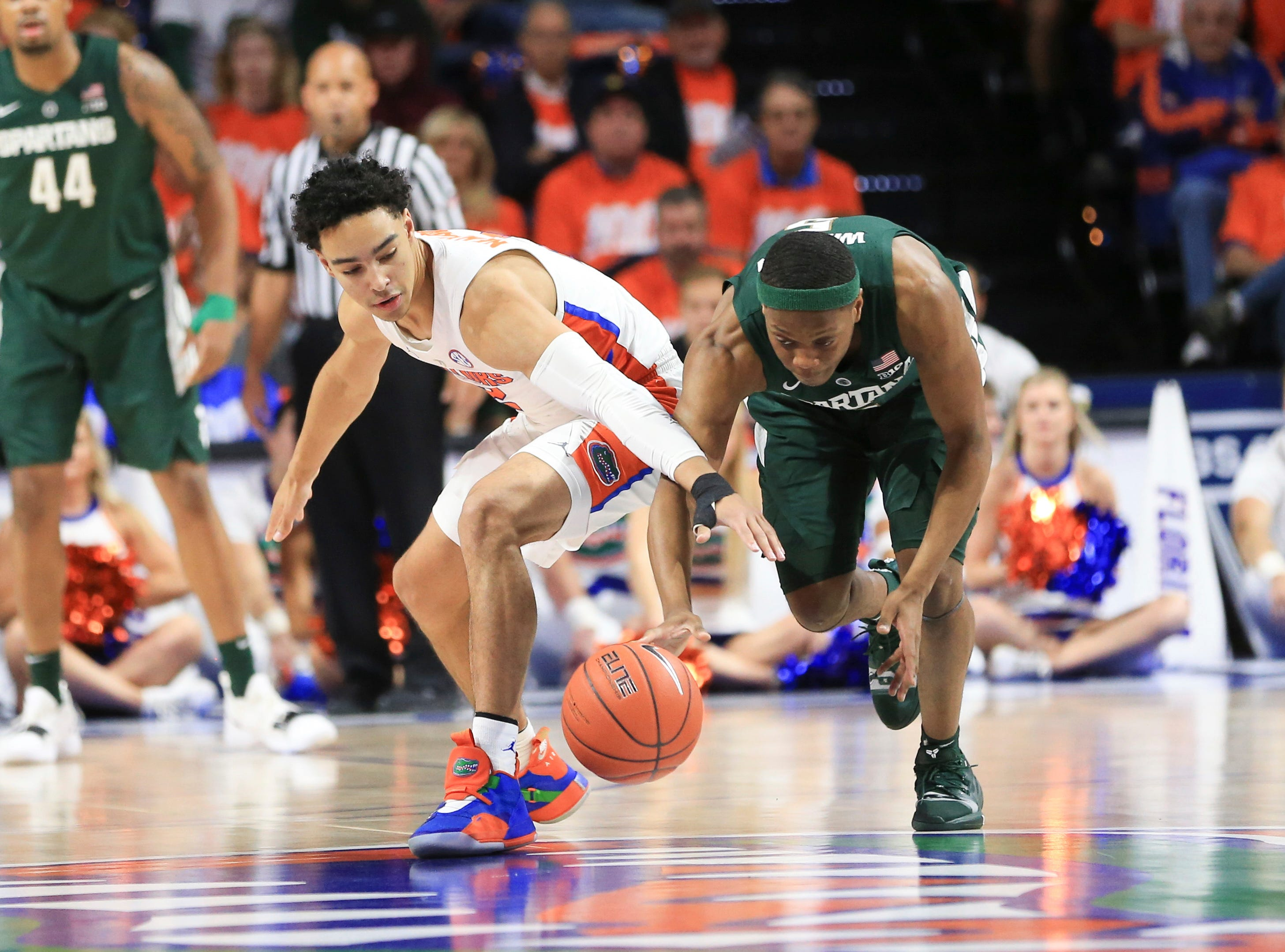 Florida guard Andrew Nembhard (2) and Michigan State guard Cassius Winston (5) go after the ball during the first half.