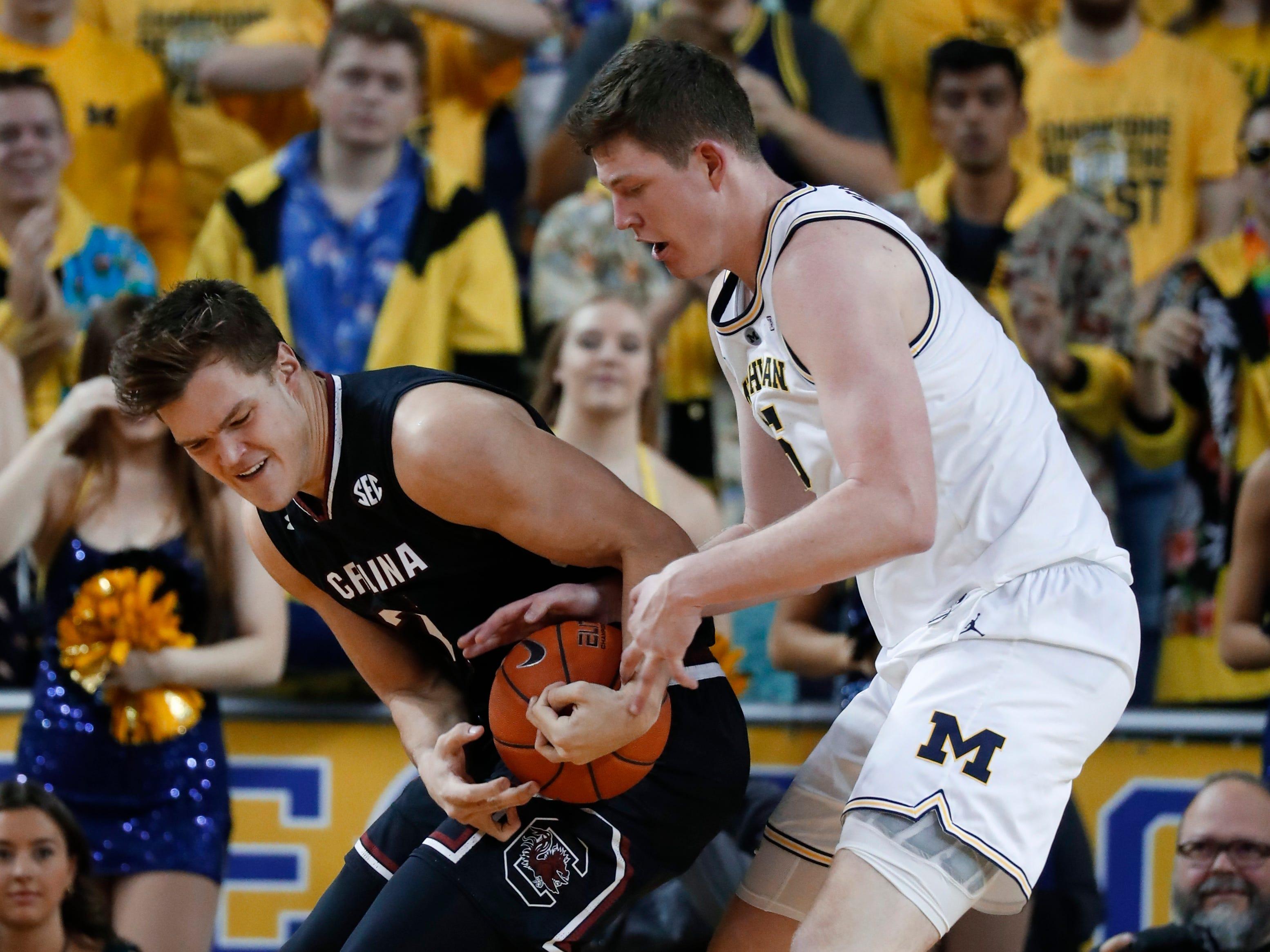 South Carolina forward Maik Kotsar (21) and Michigan center Jon Teske (15) battle for the ball in the second half.