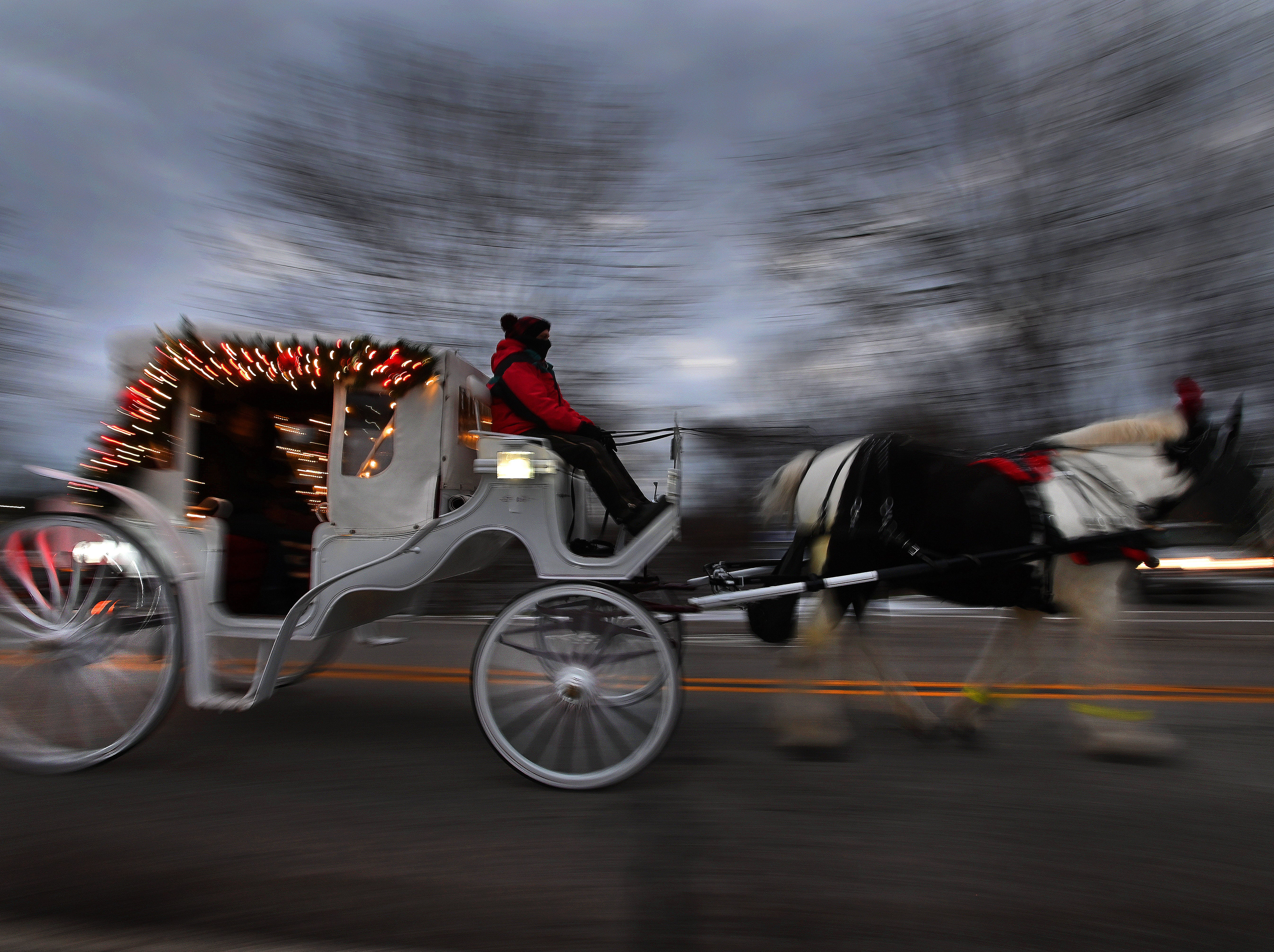 A horse-drawn carriage winds its way through Frankenmuth decked out with Christmas lights. Carriage rides, always popular in the Michigan city, take on a special glow this time of year.