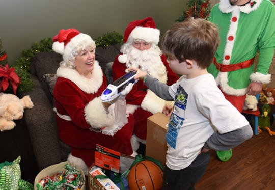Ryan Martin, 10,  plays with Santa Claus and Mrs. Claus during The Logan Foundation's holiday party at the Samaritas Center in Detroit.