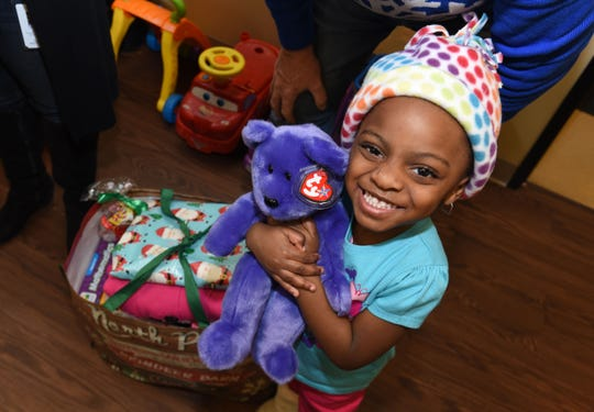 Lyric Light, 3, of Detroit, receives gifts from Santa Claus and Mrs. Claus during The Logan Foundation's holiday party at the Samaritas Center in Detroit.