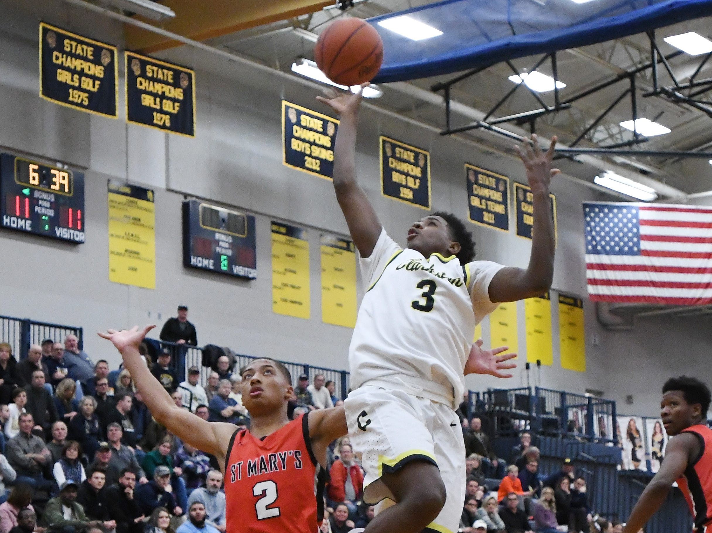 Clarkston's Desmond Millie-Bradley lays a shot up past St. Mary's Kahlil Rozier in the second quarter of their game at Clarkston High School, Friday night, December 7, 2018.