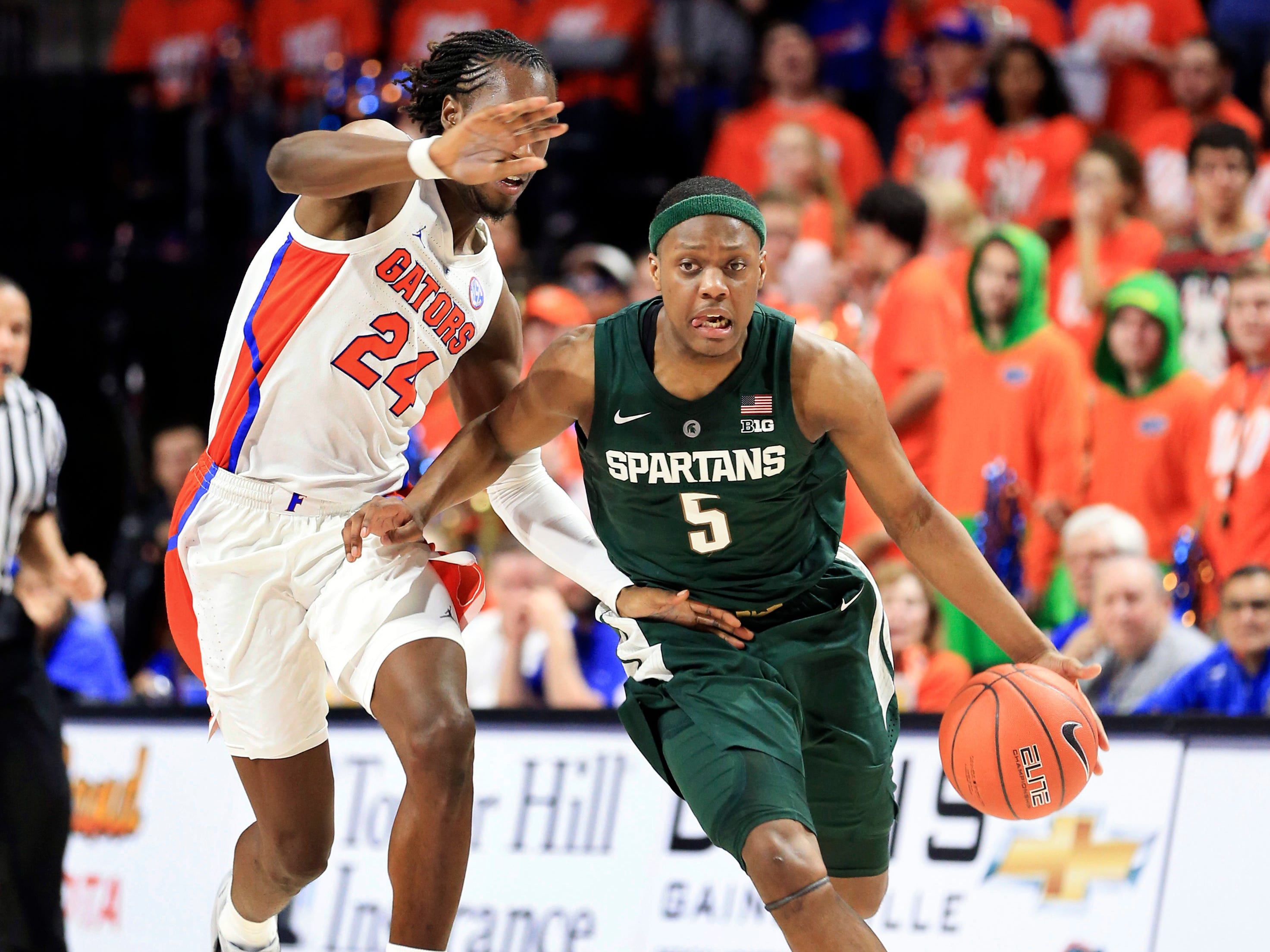 Michigan State guard Cassius Winston (5) dribbles up court past Florida guard Deaundrae Ballard (24) during the first half.