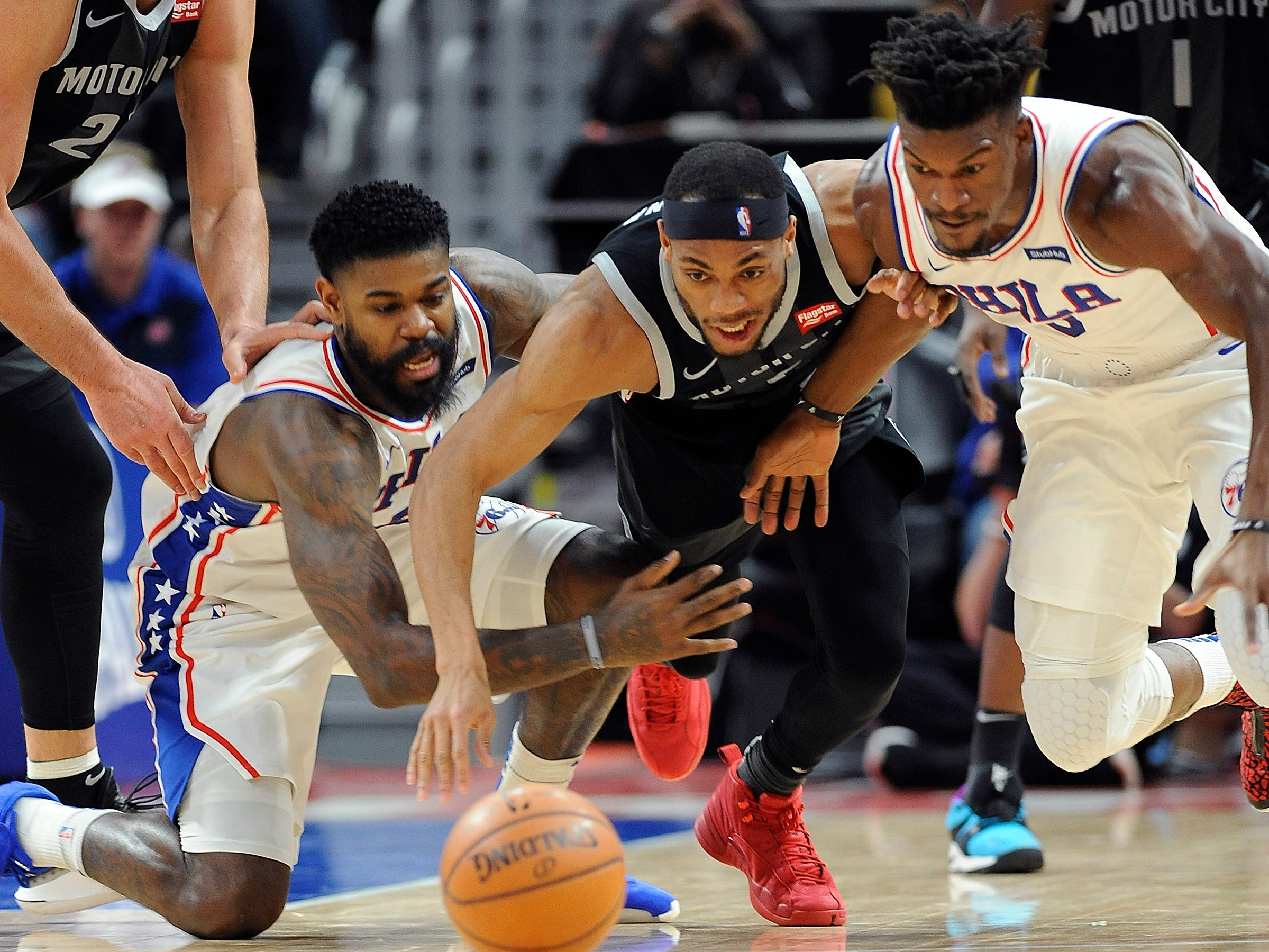 Pistons' Bruce Brown, (c), battles 76ers' l-r, Amir Johnson and Jimmy Butler for a loose ball in the second quarter.