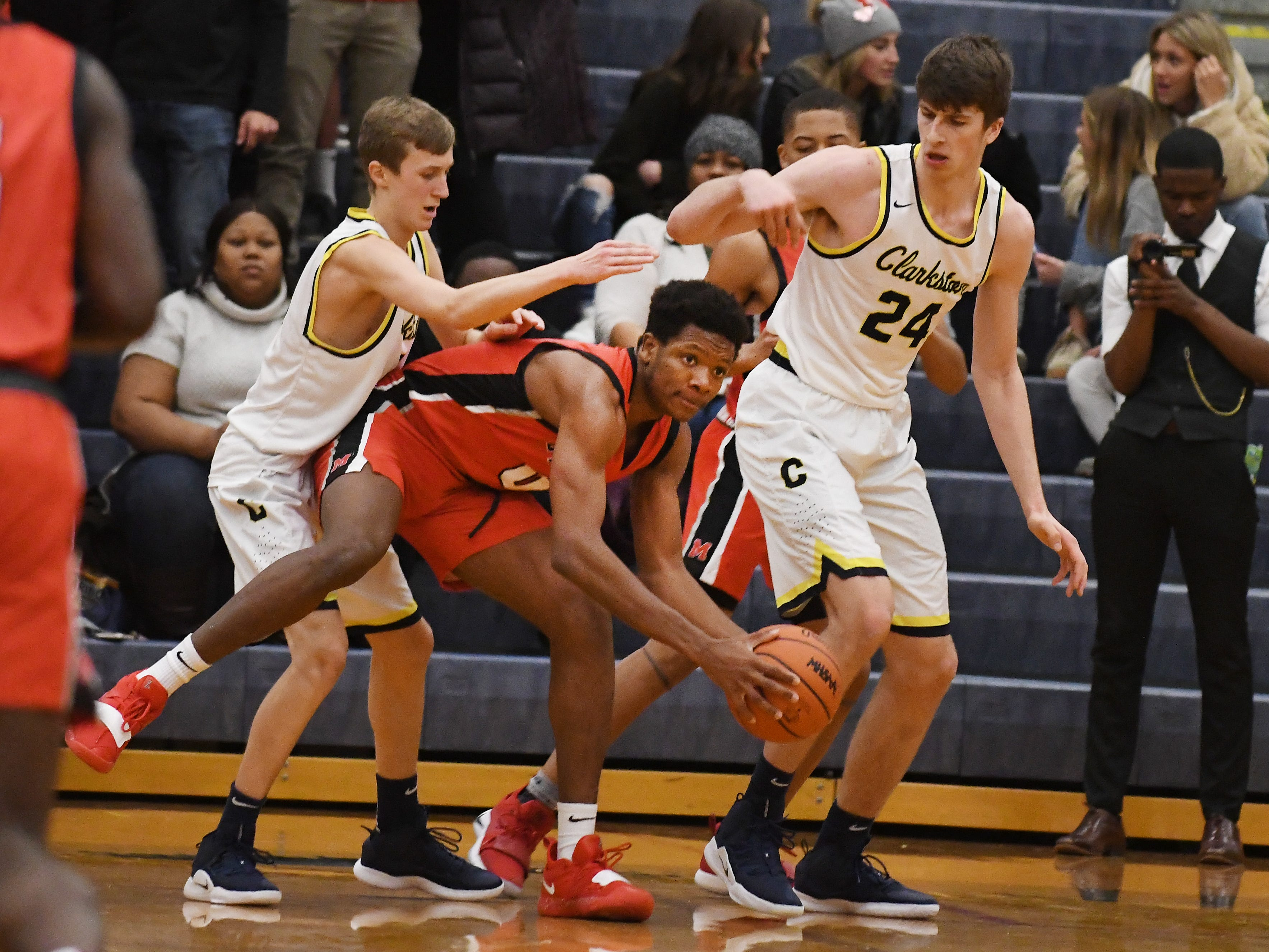 St. Mary's Peter Nwoke looks for some help with Clarkston's Flether Loyer and Mat Nicholson defending in the third quarter.