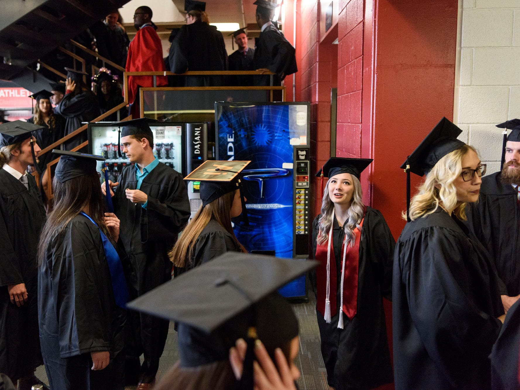 University of Southern Indiana graduates mingle as they wait for their signal to walk into the fall commencement ceremony for the College of Liberal Arts and the Romain College of Business held inside the Physical Activities Center on campus, Saturday afternoon, Dec. 8, 2018.
