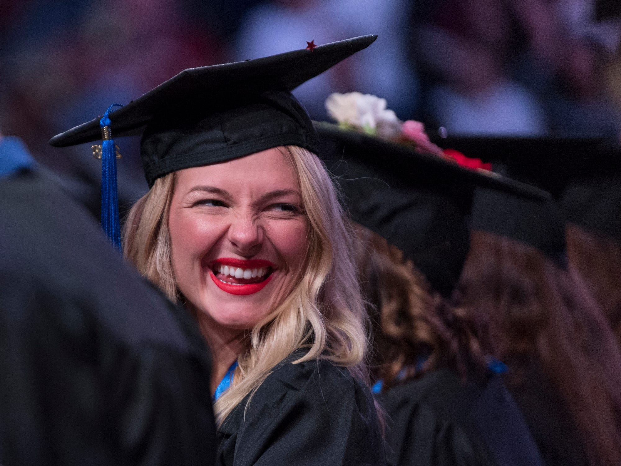 Brittany Curtis of Evansville smiles at her family during the fall commencement ceremony for the University of Southern Indiana's College of Liberal Arts and the Romain College of Business inside the school's Physical Activities Center in Evansville, Ind., Saturday, Dec. 8, 2018. Curtis majored in public relations and advertising and graduated with a Bachelor of Science from the College of Liberal Arts.