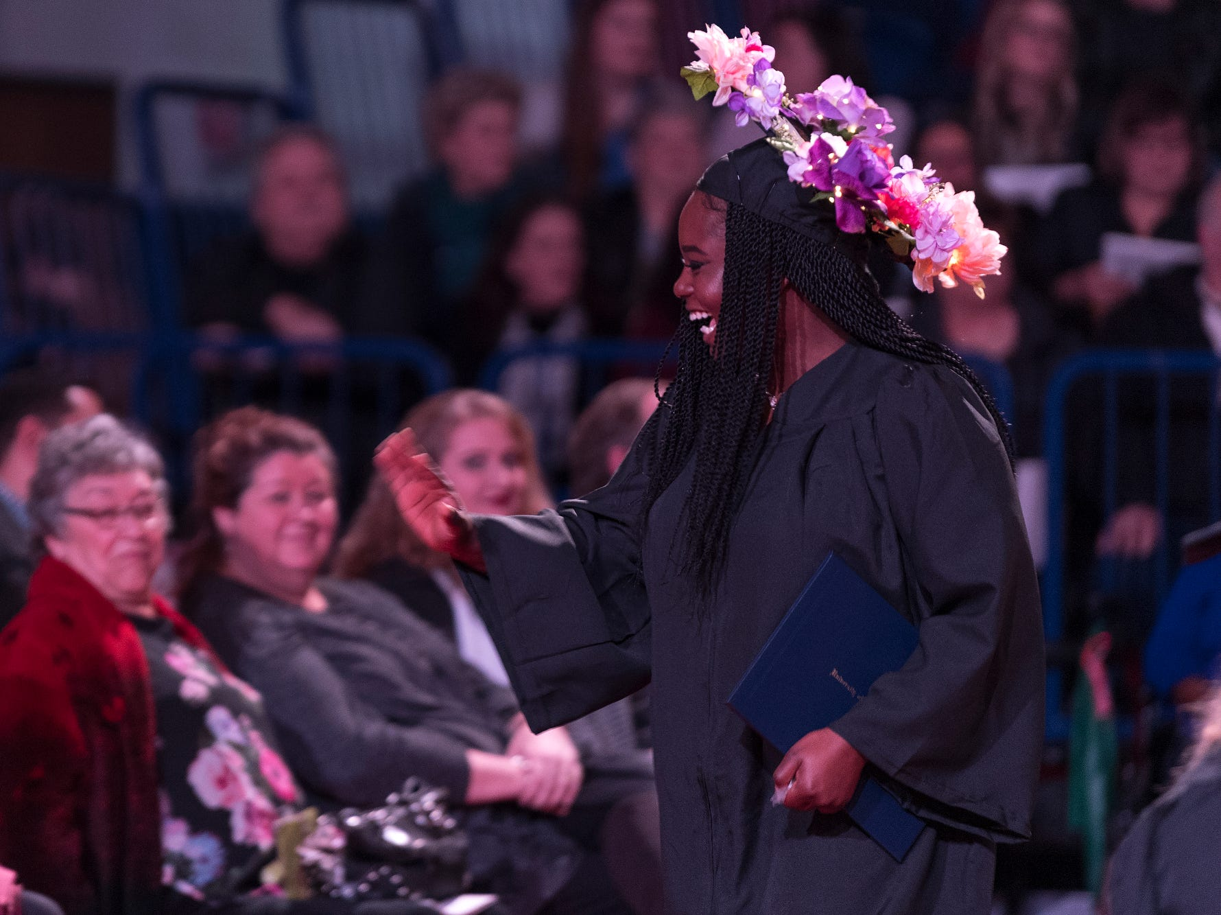"""Lilly ChaNell Howard of Alton, Ill., waves to an audience member as she walks back to her seat during the fall commencement ceremony for the University of Southern Indiana's College of Liberal Arts and the Romain College of Business at the school's Physical Activities Center in Evansville, Ind., Saturday, Dec. 8, 2018. The Bachelor of Science graduate's cap had the phrase """"every end is a new beginning"""" written in gold on the top."""