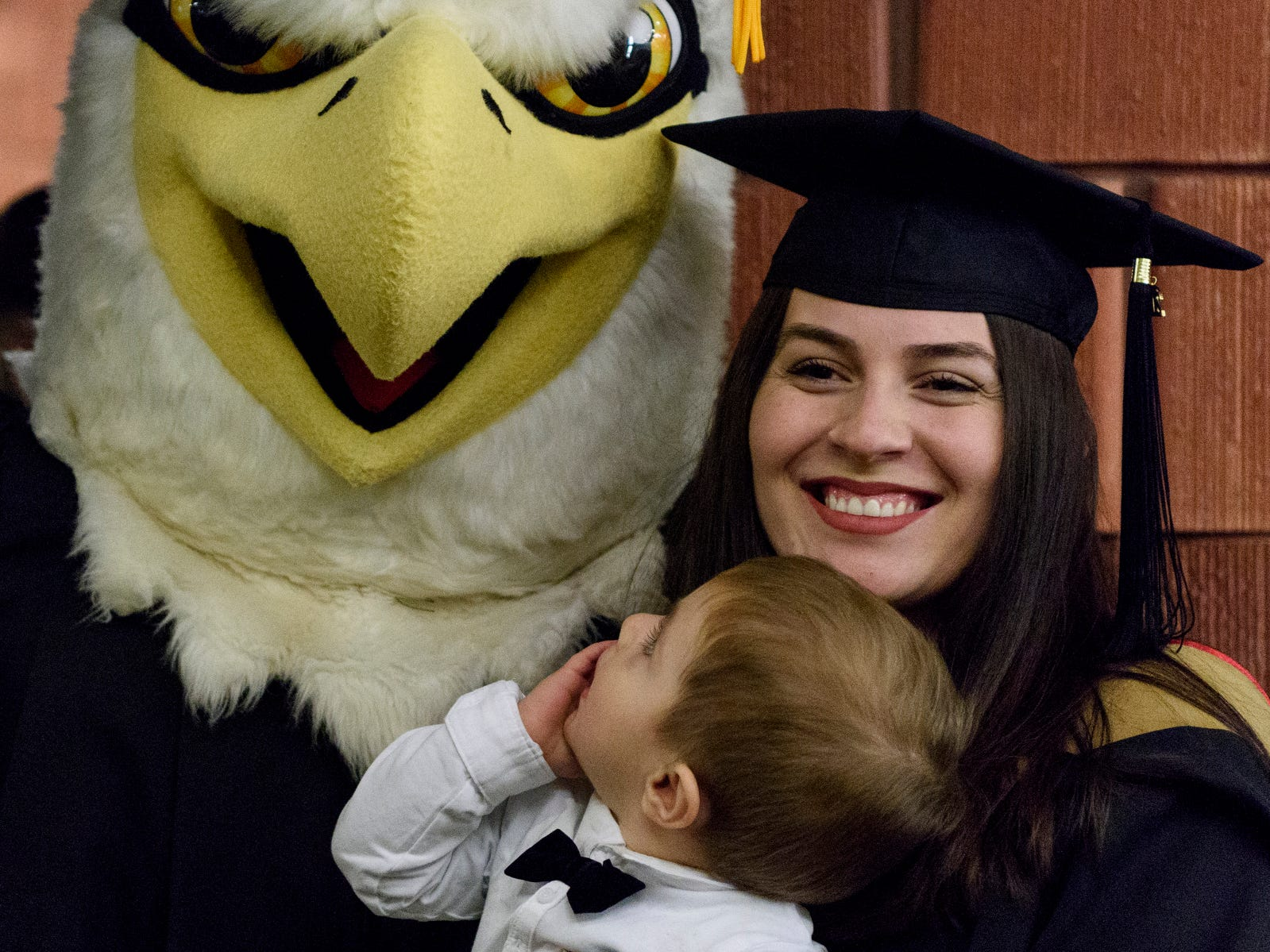 Master of Business Administration graduate Krenare Shala of Prishtina, Kosovo, poses for a picture with her son Lir Dragusha and Archie, the University of Southern Indiana mascot, following the fall commencement ceremony for USI's College of Liberal Arts and the Romain College of Business, Saturday afternoon, Dec. 8, 2018.