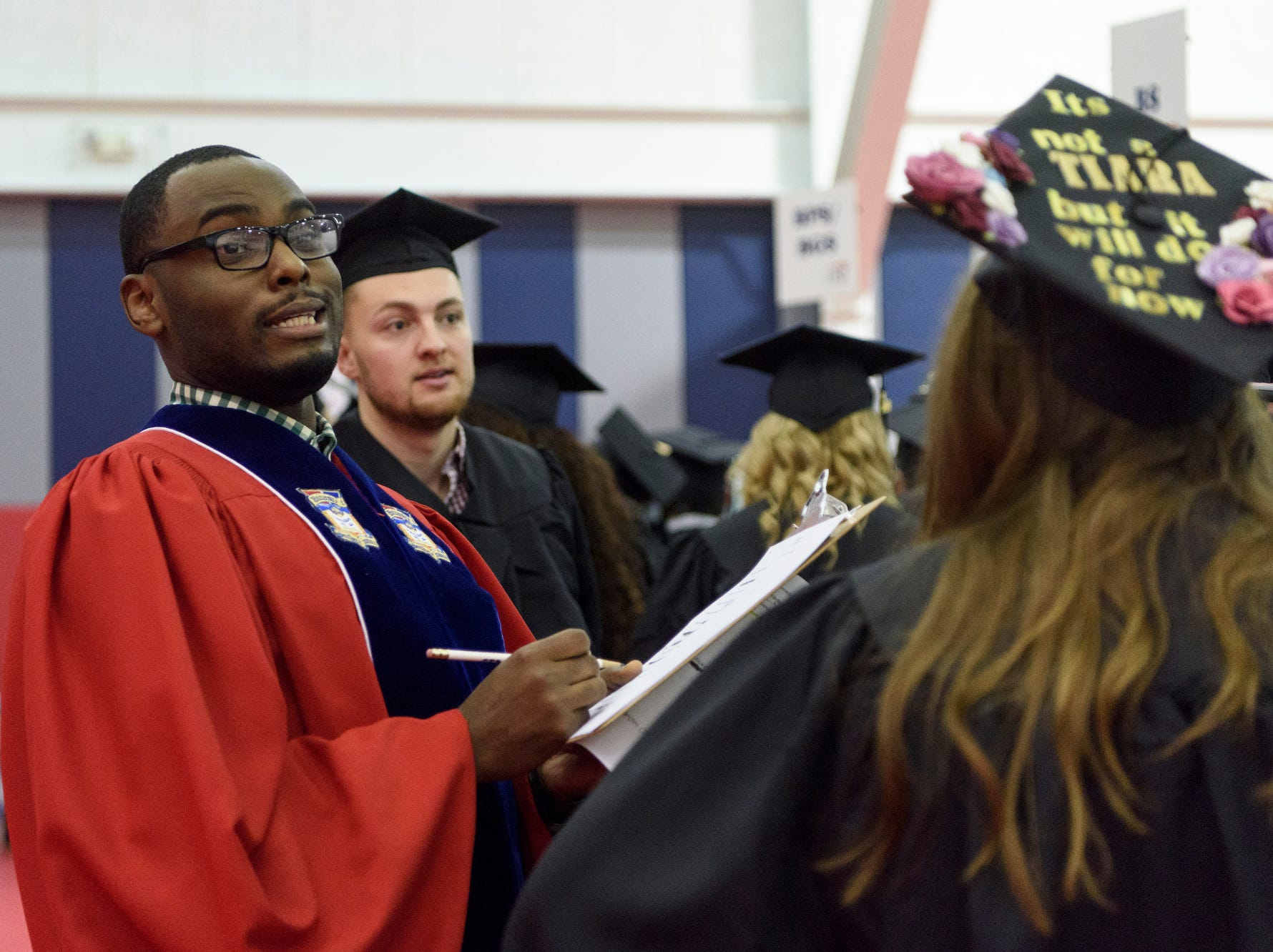 D'Angelo Taylor, Assistant Director of the Multicultural Center at the University of Southern Indiana, performs a name check with graduates in line for USI's fall commencement ceremony for the College of Liberal Arts and the Romain College of Business held on campus in Evansville, Ind., Saturday, Dec. 8, 2018.