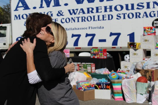 Molly Lord of United Way of the Big Bend embraces Graham in celebration of the success of the toy drive.