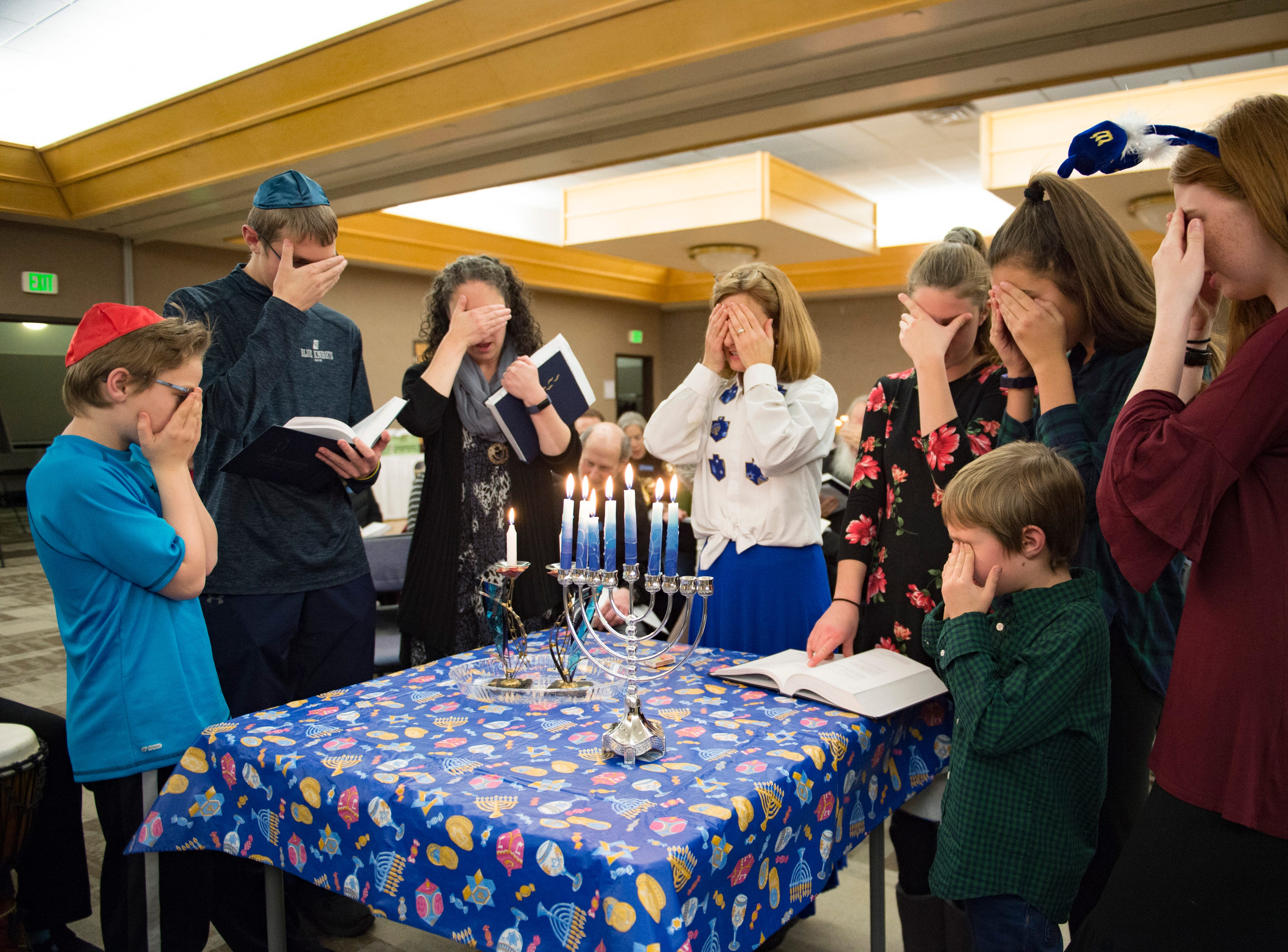 A group lights the Shabbat candles on the sixth night of Hanukkah during a family gathering with Temple Or Hadash at the Fort Collins Senior Center on Friday, December 7, 2018.