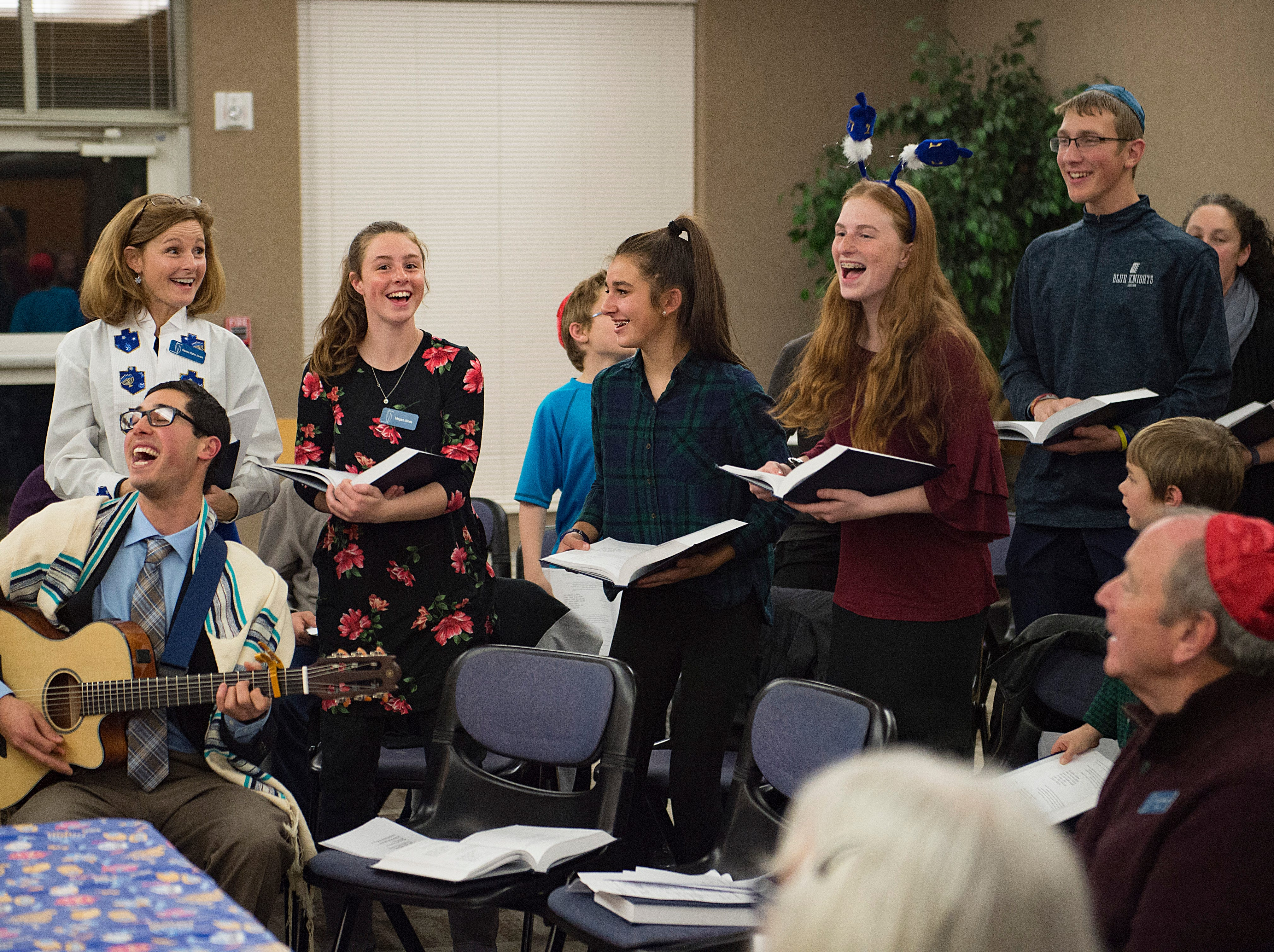 People sing songs during Shabbat services on the sixth night of Hanukkah during a family gathering with Temple Or Hadash at the Fort Collins Senior Center on Friday, December 7, 2018.