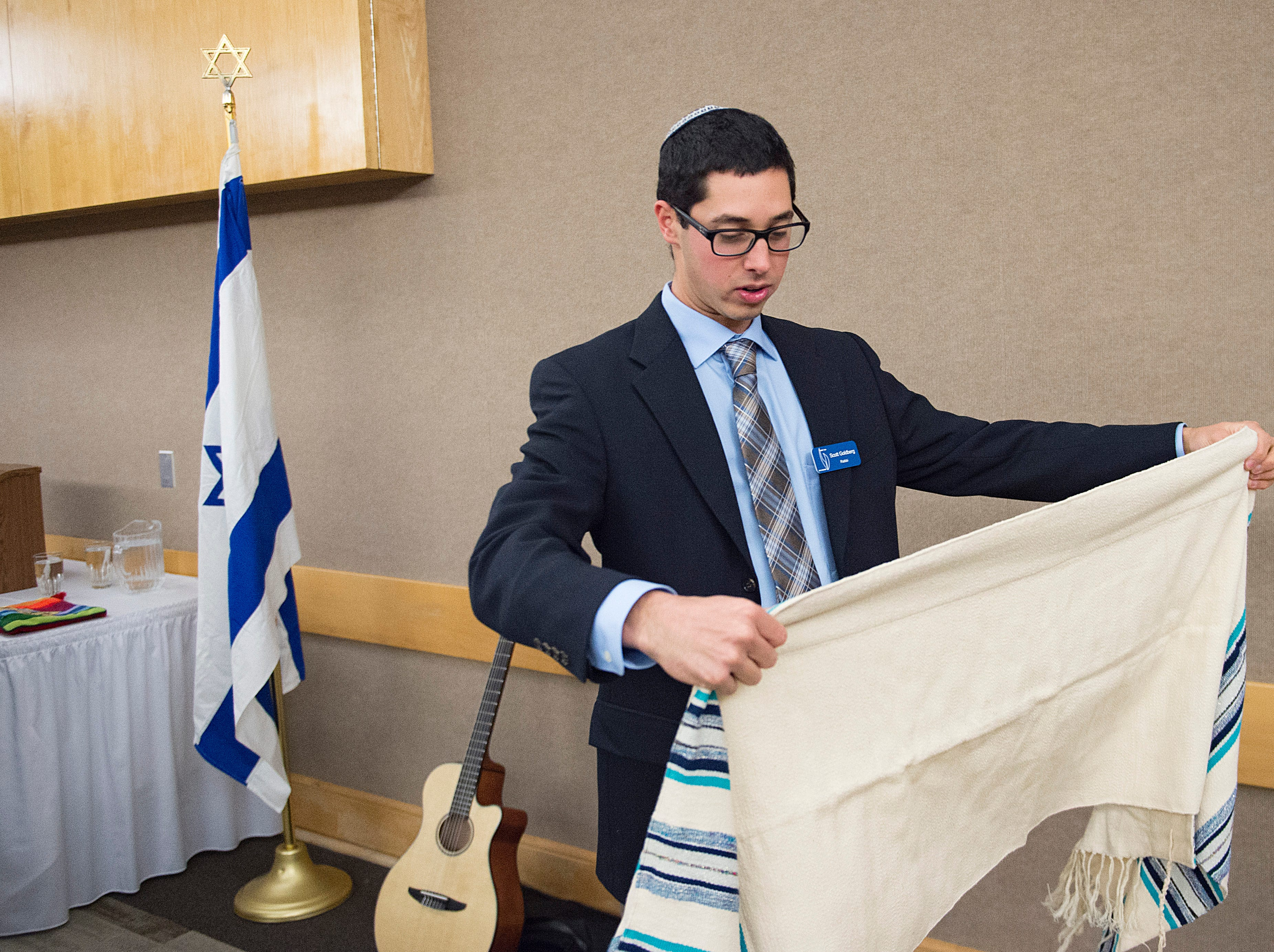 Student rabbi Scott Goldberg prepares his tallit before shabbat services  on the sixth night of Hanukkah during a family gathering with Temple Or Hadash at the Fort Collins Senior Center on Friday, December 7, 2018.