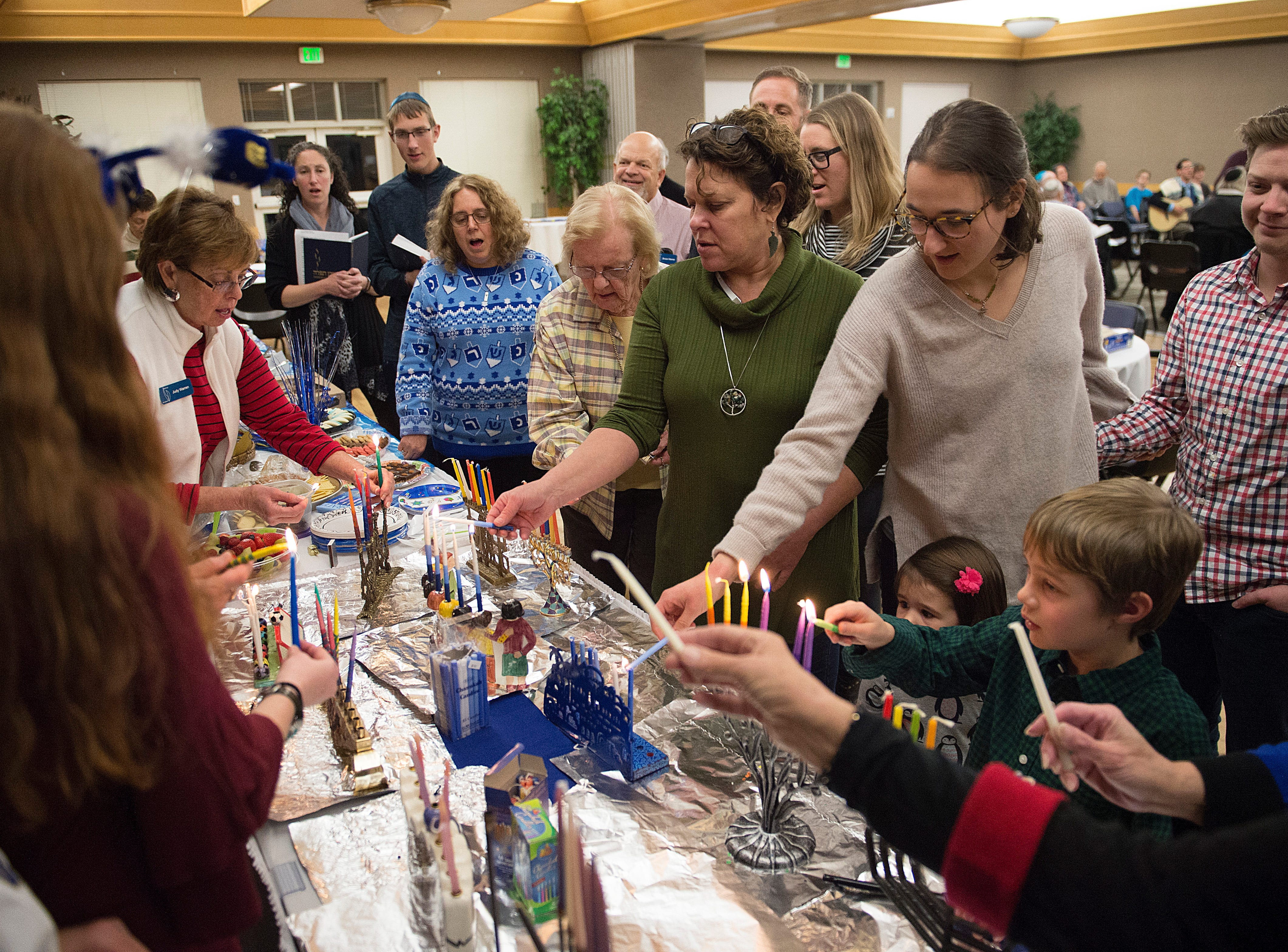 Candles are lit on menorahs on the sixth night of Hanukkah during a family gathering with Temple Or Hadash at the Fort Collins Senior Center on Friday, December 7, 2018.