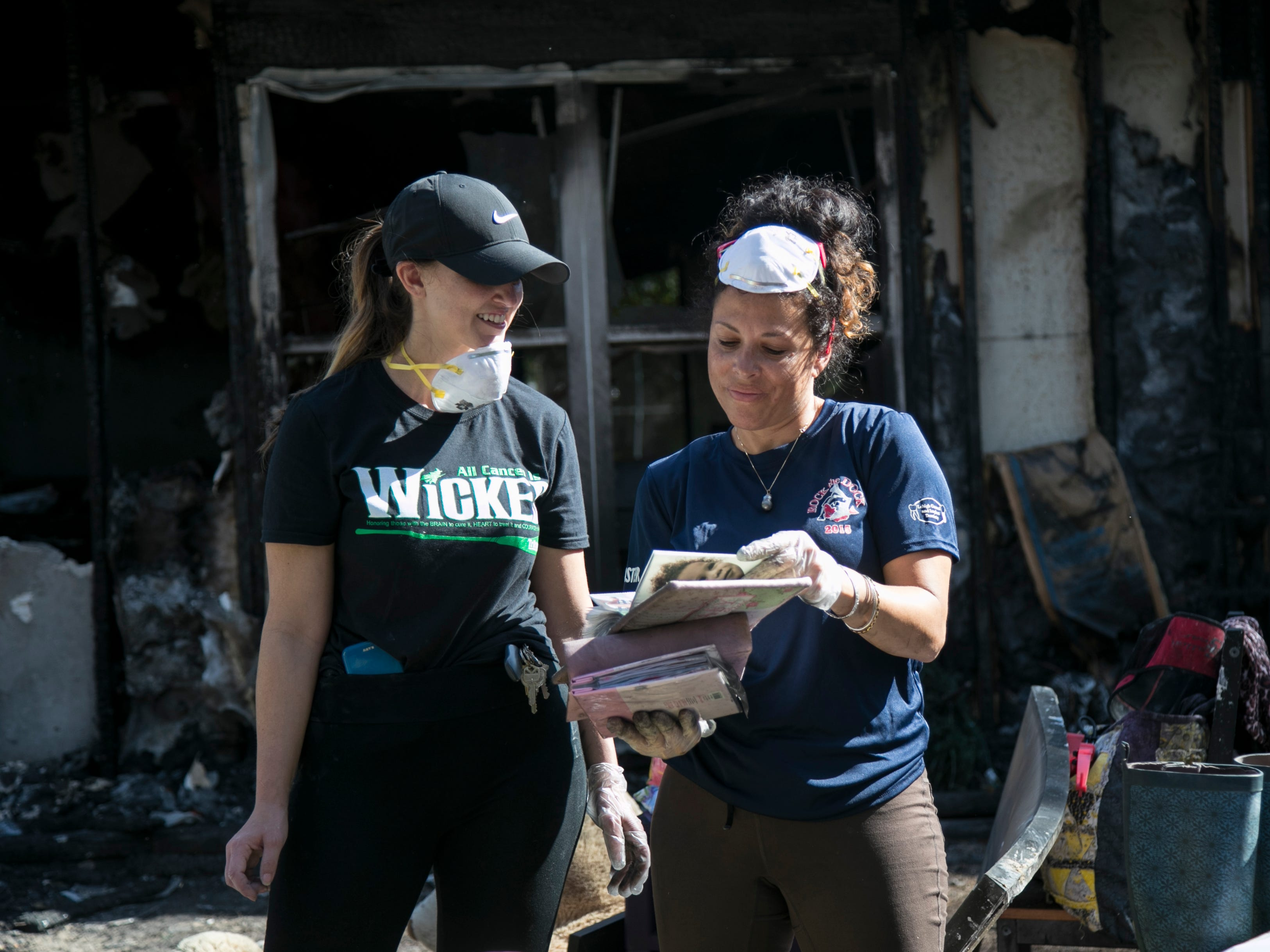 Marliss Brockington, right, shows Nicole Buchanan some of the family photos they saved from their home after a fire earlier this week. The home was a total loss.