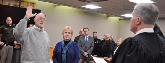 Oconto County Clerk of Court Mike Hodkiewicz takes the oath of office Friday from Judge Jay N. Conley at the Oconto County Courthouse. Next to Hodkiewicz is his wife, Mary Ann.