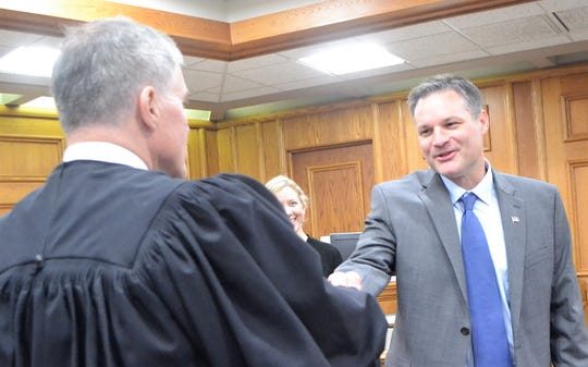 Oconto County Sheriff-elect Todd Skarban is congratulated by Judge Jay N. Conley, after administering the oath of office to Skarban on Friday. At center is Skarban's wife Heather.