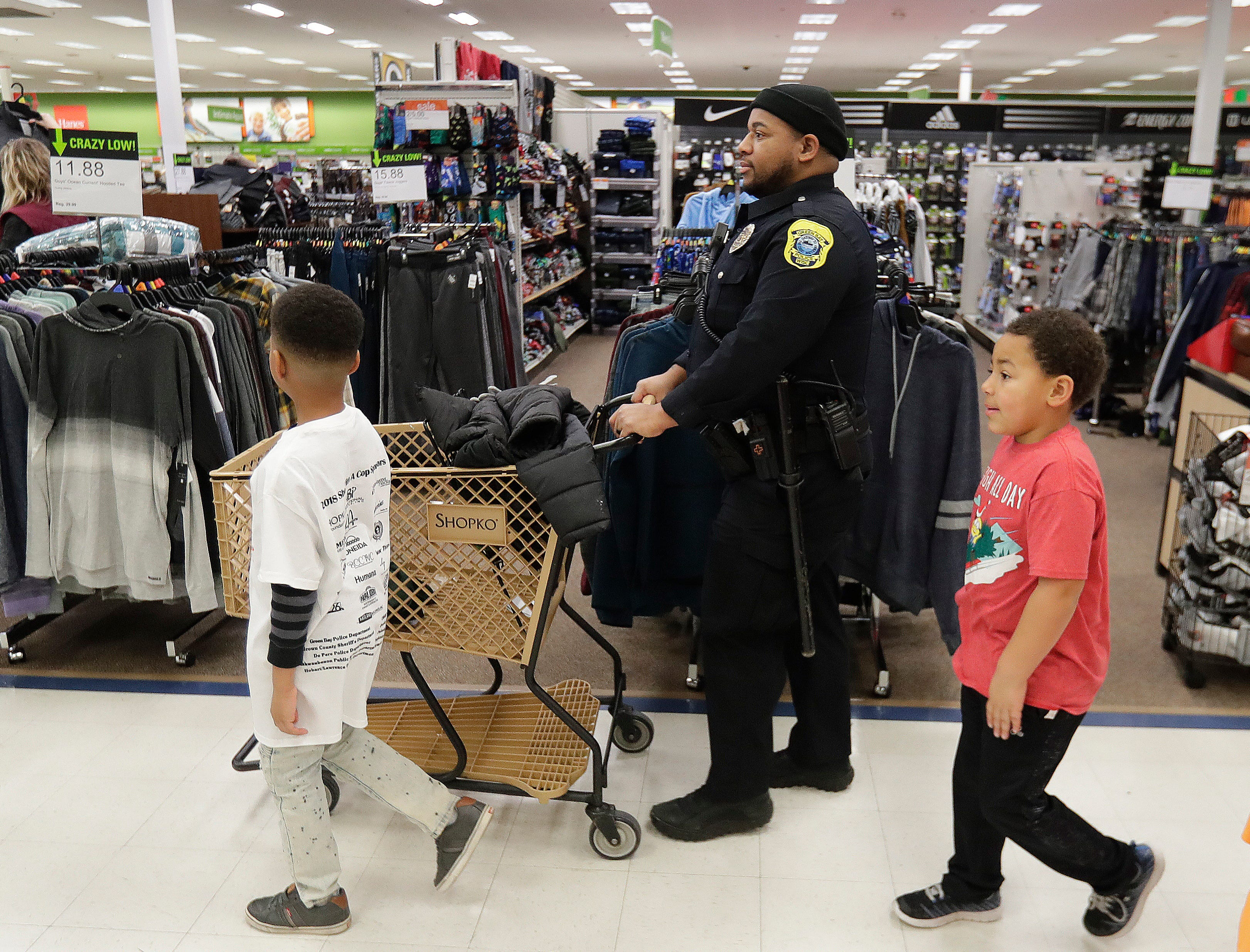 Green Bay Police Department Officer Aaron Walker shops with his Shop with A Cop program kids at Shopko on East Mason Street December 8, 2018 in Green Bay, Wis.