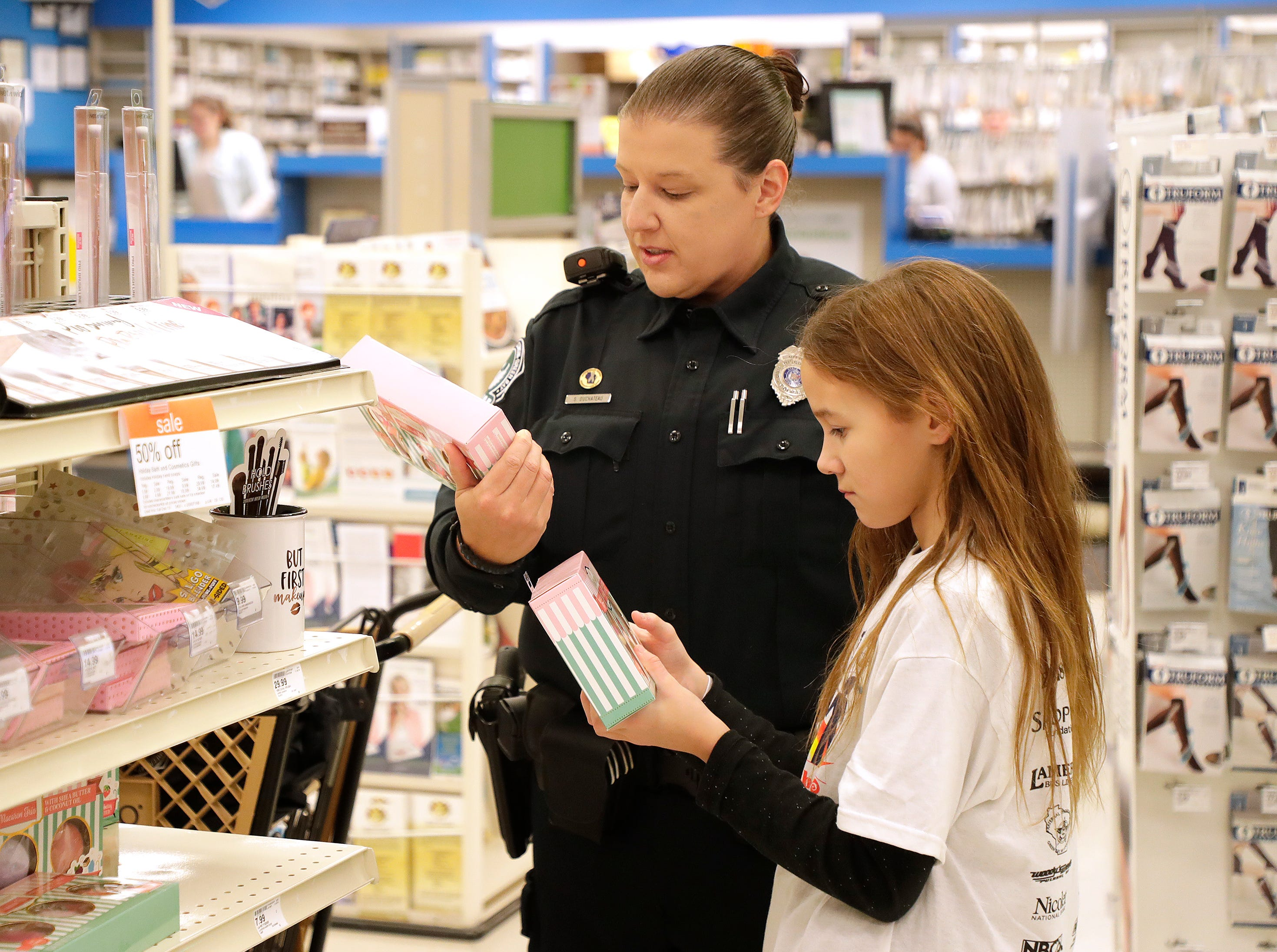 University of Wisconsin Green Bay Police Department Officer Sabrina Duchateau selects gifts with her Shop with A Cop program kid at Shopko on East Mason Street December 8, 2018 in Green Bay, Wis.