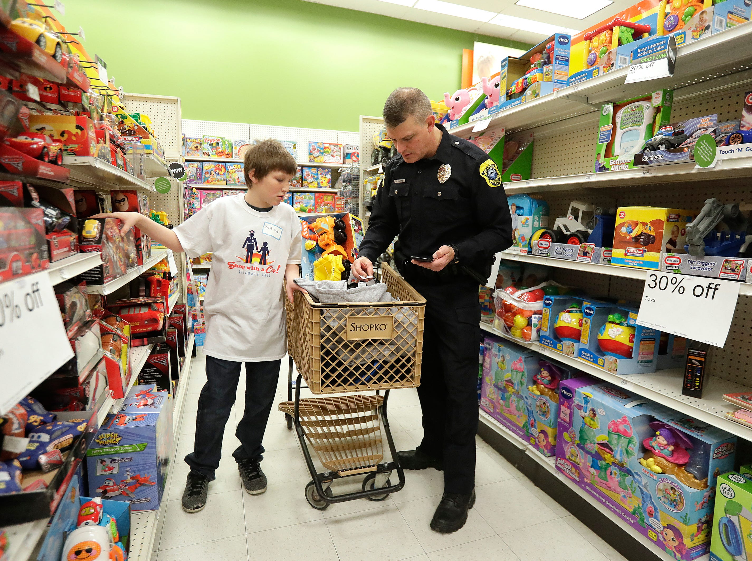 Green Bay Police Department Officer Officer Daniel Yantes shops with his Shop with A Cop program kid at Shopko on East Mason Street December 8, 2018 in Green Bay, Wis.