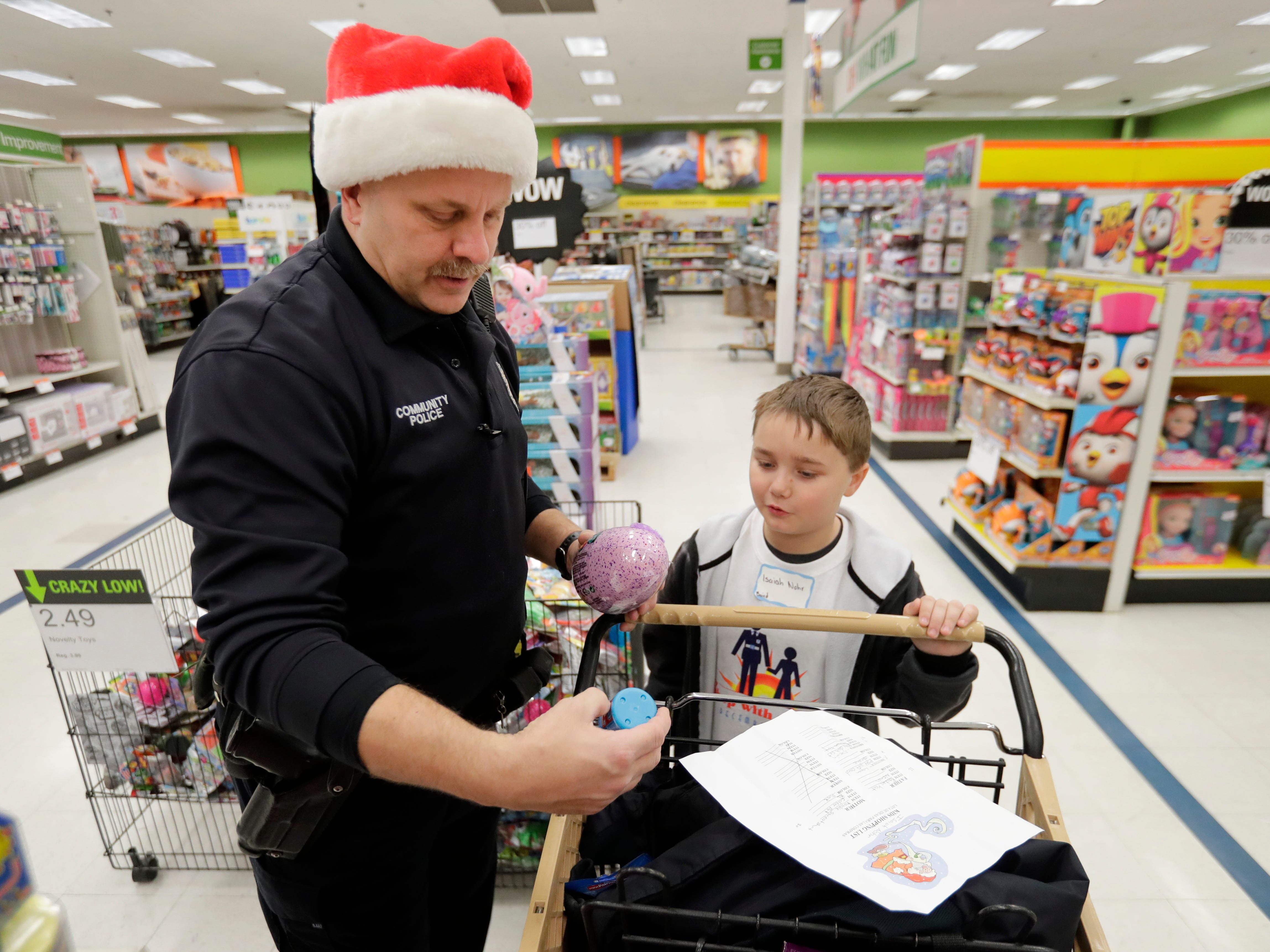 Green Bay Police Department Officer Scott Schuetze shops with his Shop with A Cop program kid at Shopko on East Mason Street December 8, 2018 in Green Bay, Wis.