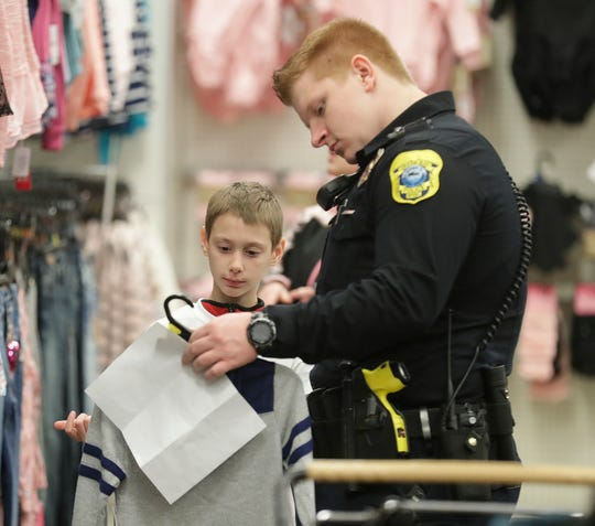 Green Bay Police Department Officer Kevin Stevens selects gifts in December 2018 with his Shop with A Cop program participant at Shopko on East Mason Street in Green Bay. Shopko for years has been a partner in the Shop with a Cop program.