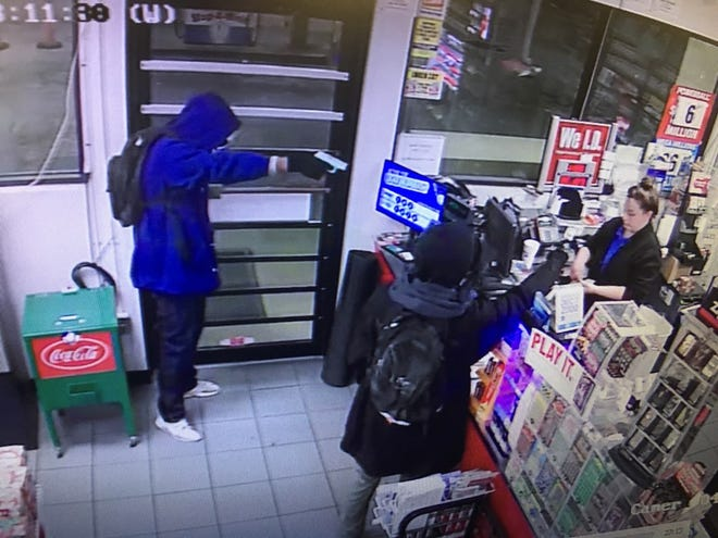 Surveillance photos from the Stop-A-Minit on South Piedmont Highway show two armed suspects demanding money from a store employee late Friday.