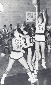 Morley Denning of Simms fires a jumper as Kim Breidenbach (42) boxes out during a Class B high school game in the mid-1980s.